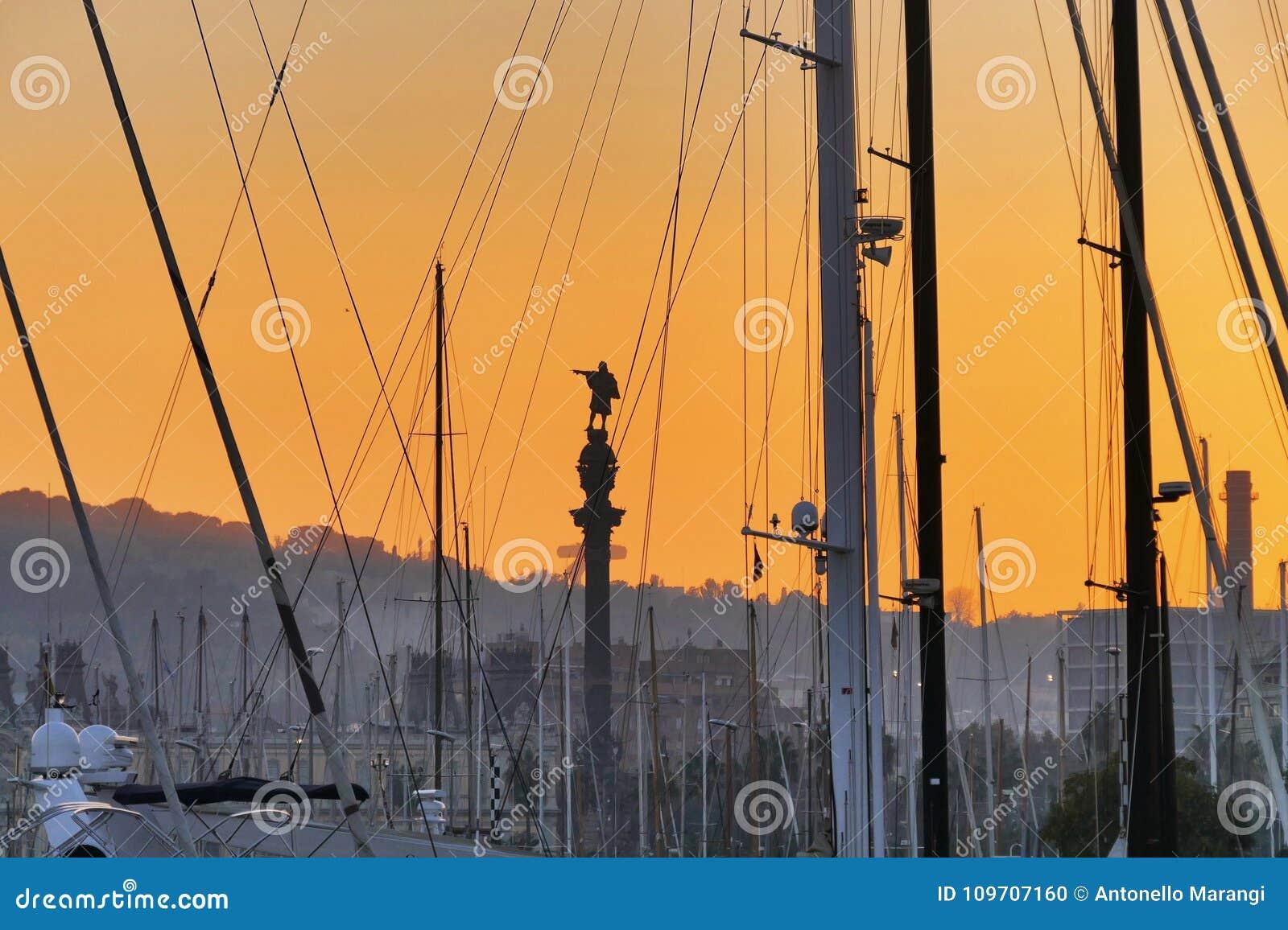 La vue de silhouette de statue de Columbus par des arbres et des linceuls des bateaux a amarré dans le port au coucher du soleil