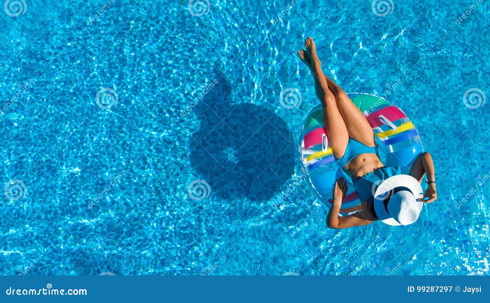 La vue supérieure aérienne de la belle fille dans la piscine d en haut, détendent le bain sur le beignet gonflable d anneau dans
