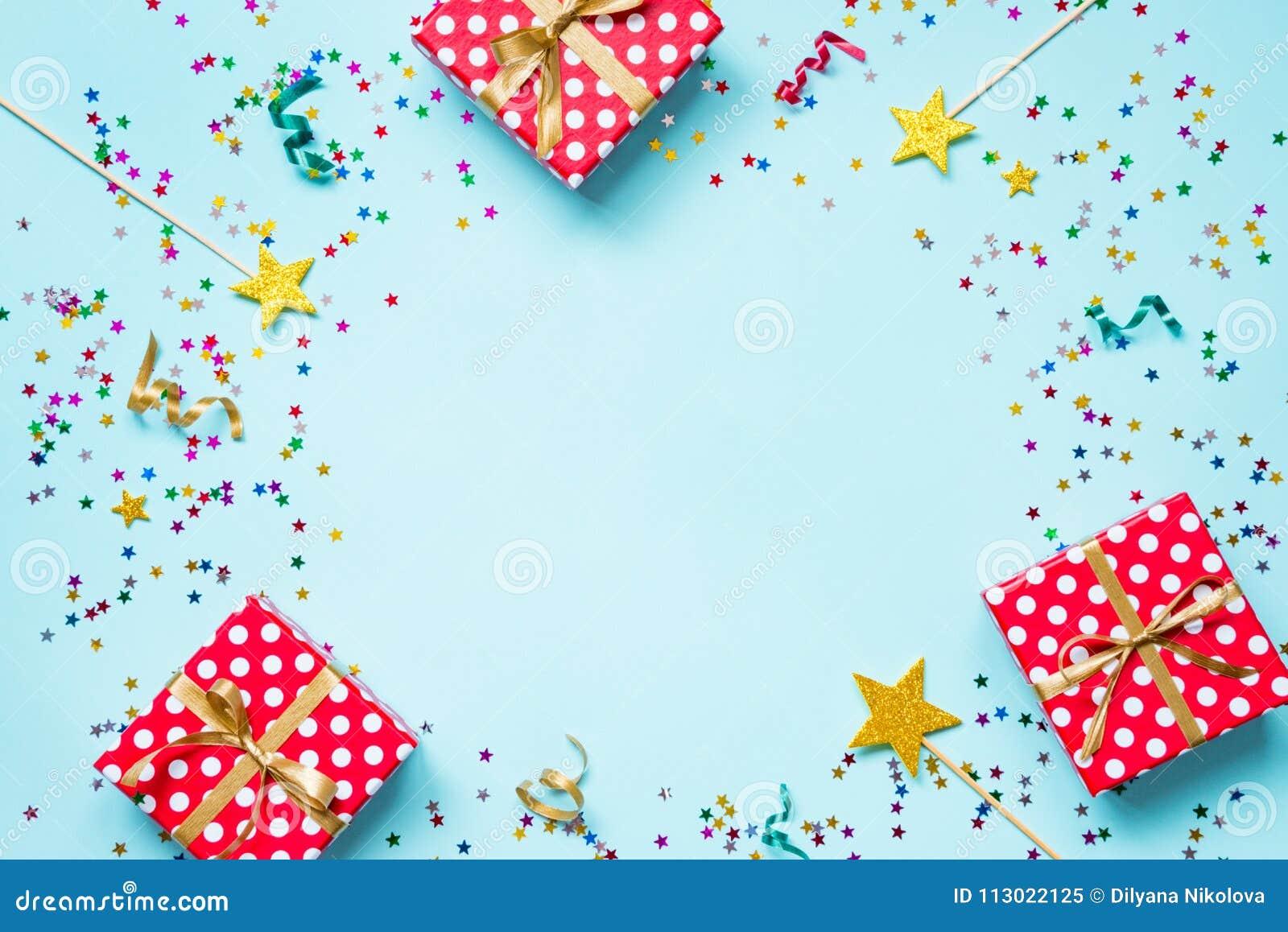 La vue supérieure d un rouge a pointillé des boîte-cadeau, des baguettes magiques magiques d or, des confettis colorés et des rub