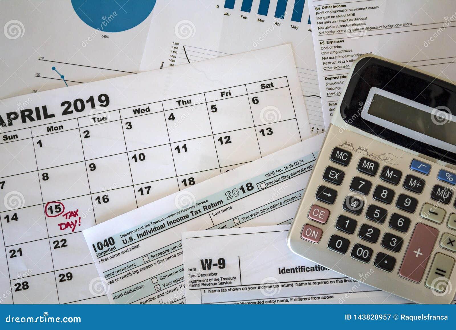 La vue supérieure de la calculatrice, des feuilles d impôt, des graphiques et de la feuille de calendrier avec la date d impôts a