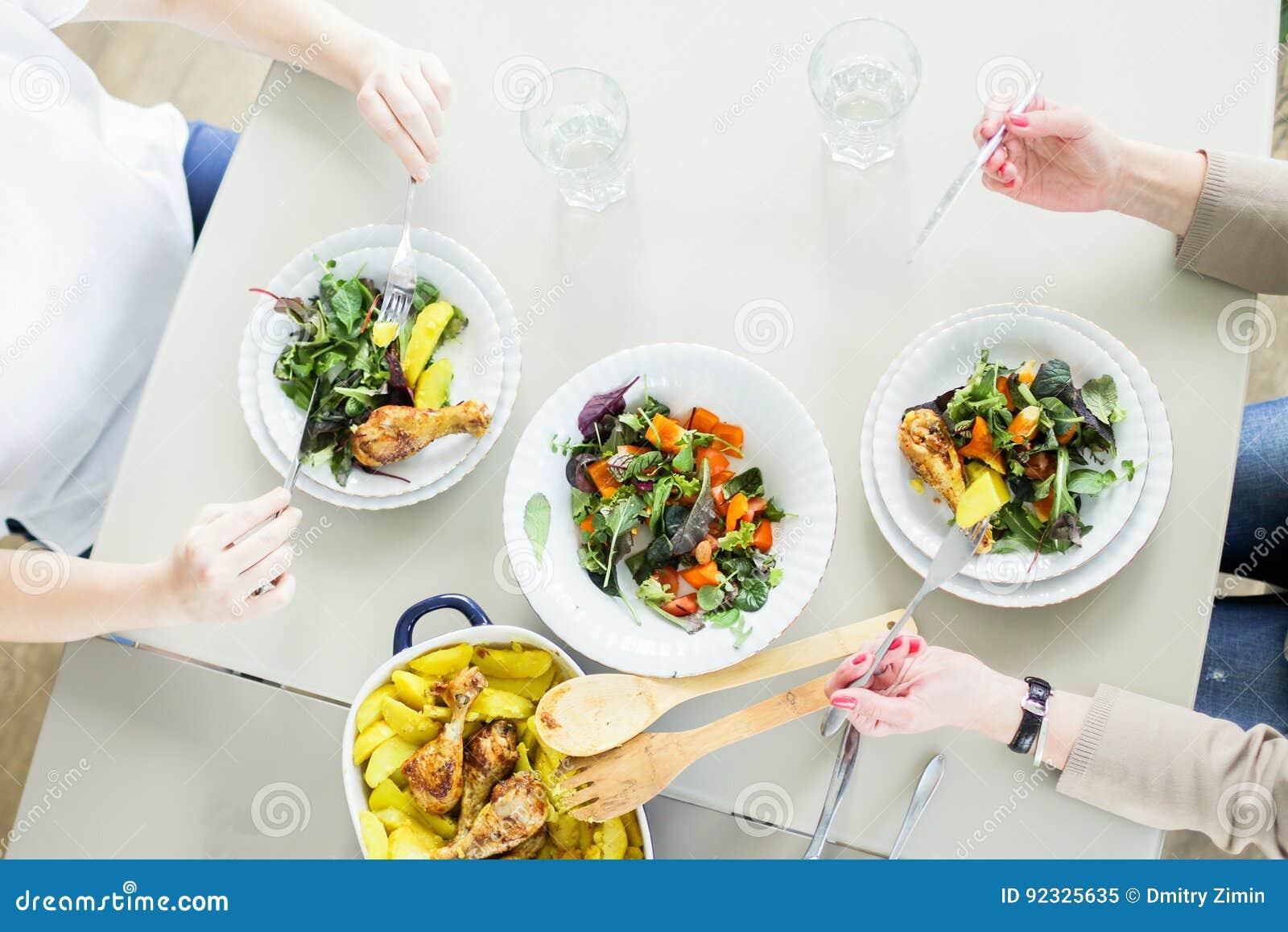 La vue supérieure de deux jeunes femmes mangeant des salades vertes avec chiken et pomme de terre