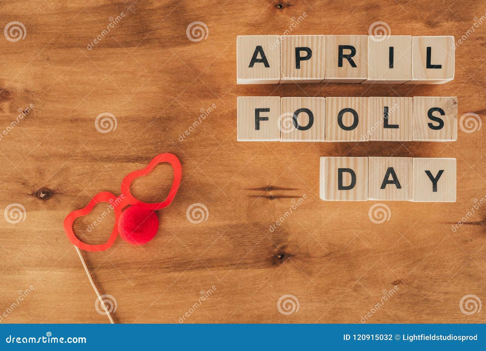 La vue supérieure des cubes en bois disposés dupe en avril le lettrage de jour avec des lunettes de partie et le nez de clown sur