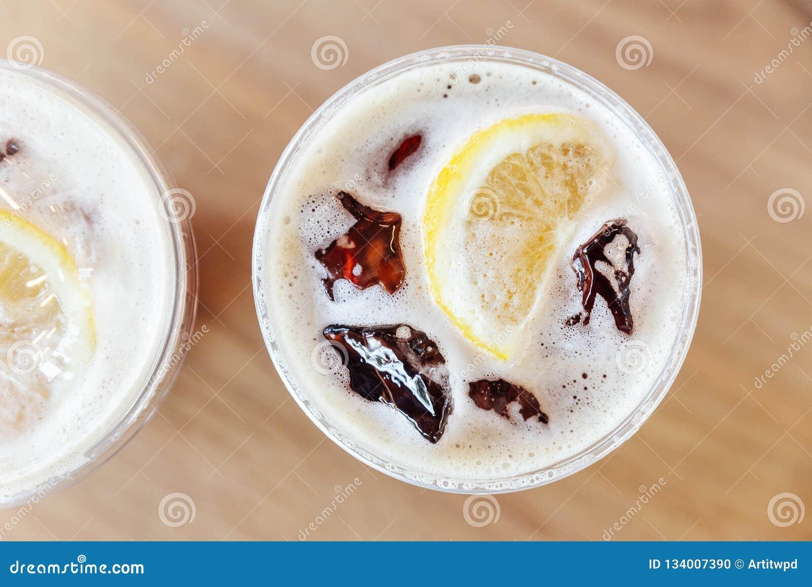 La vue supérieure du froid nitro Iced préparent le café avec le citron sur la table en bois