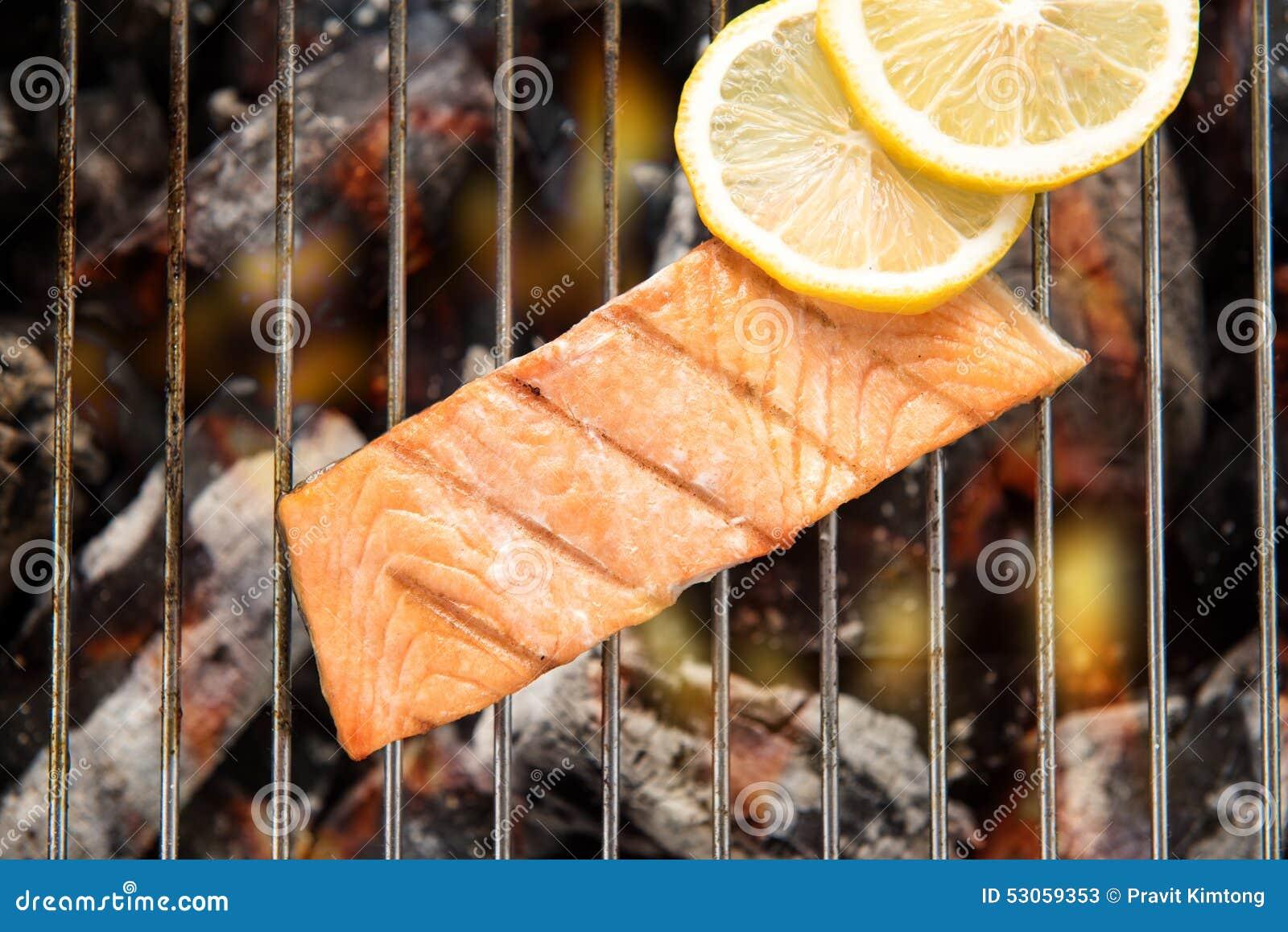 La vue supérieure a grillé des saumons avec le citron sur le gril flamboyant