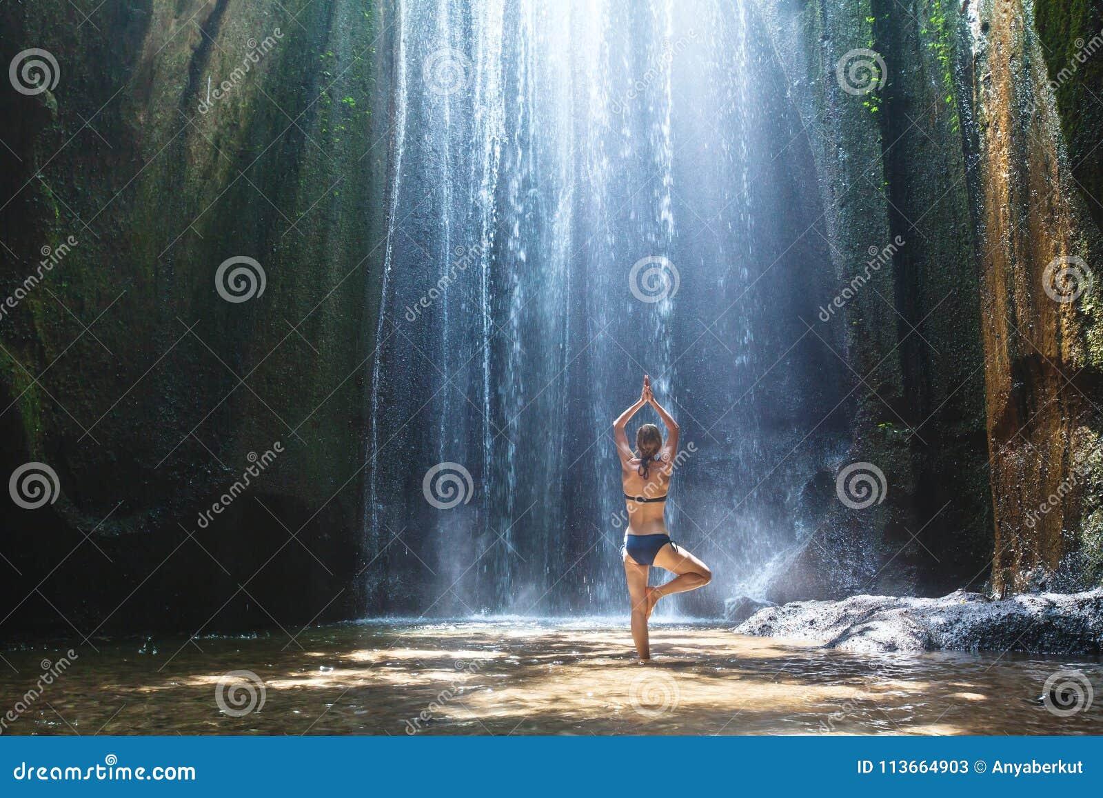 La yoga, mujer hermosa practica en armonía de la cascada, del cuerpo y de la mente
