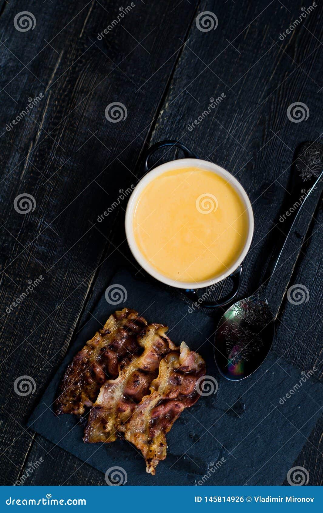 La zucca passa la minestra con bacon fritto su fondo nero