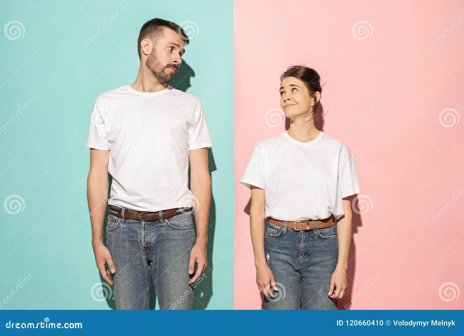 Laat me denken Twijfelachtig peinzend paar met nadenkende uitdrukking die keus maken tegen roze achtergrond