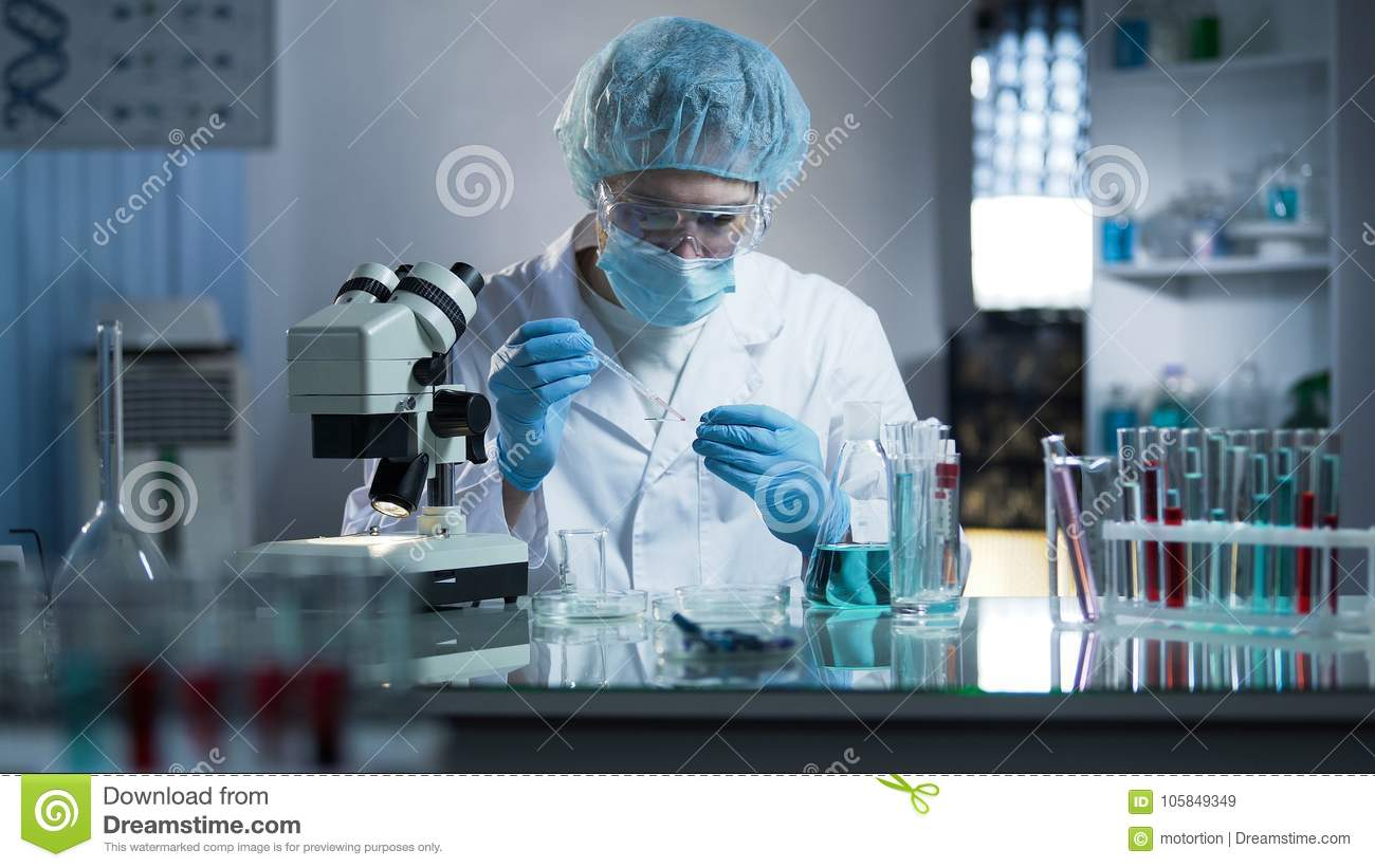 Lab worker dripping sample onto laboratory glass to research cloning process