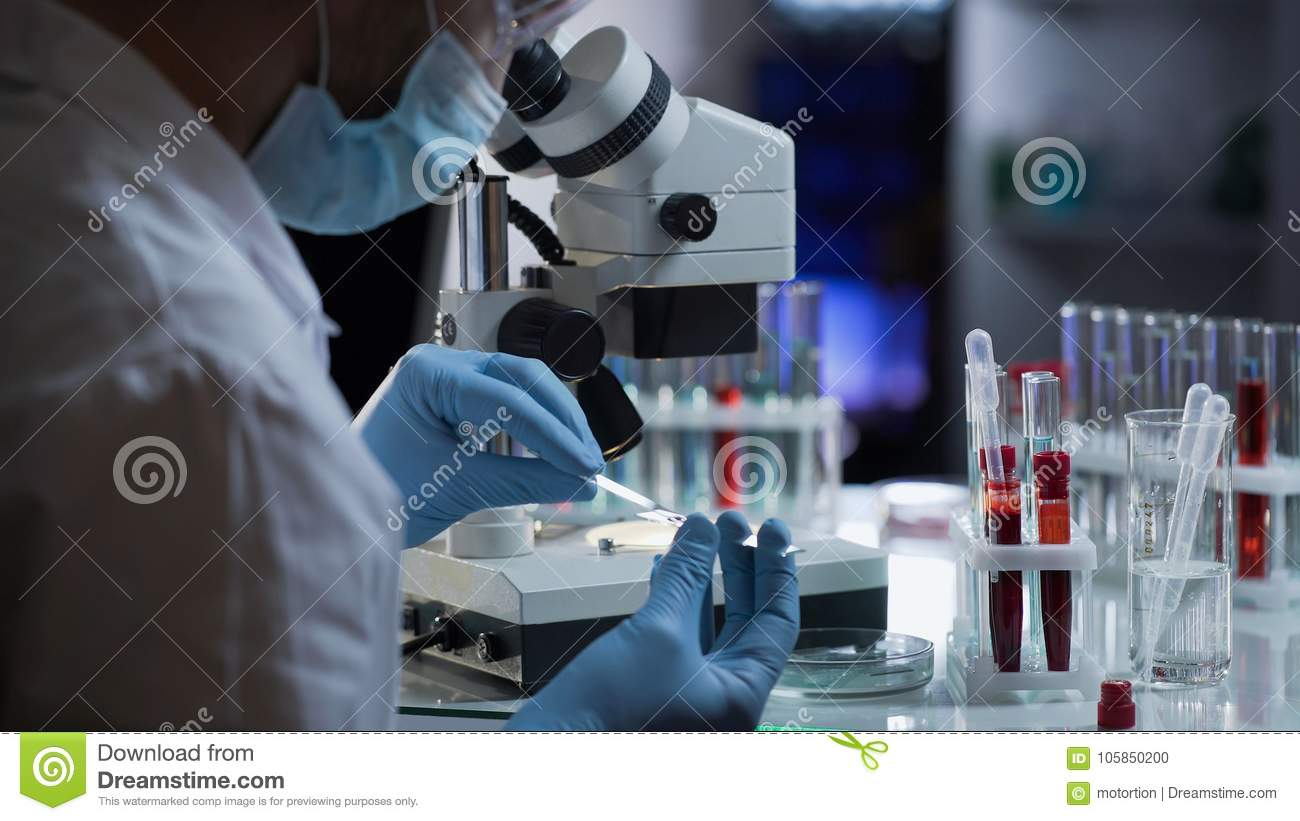 Lab worker preparing glass with blood for detection of antibodies and infections