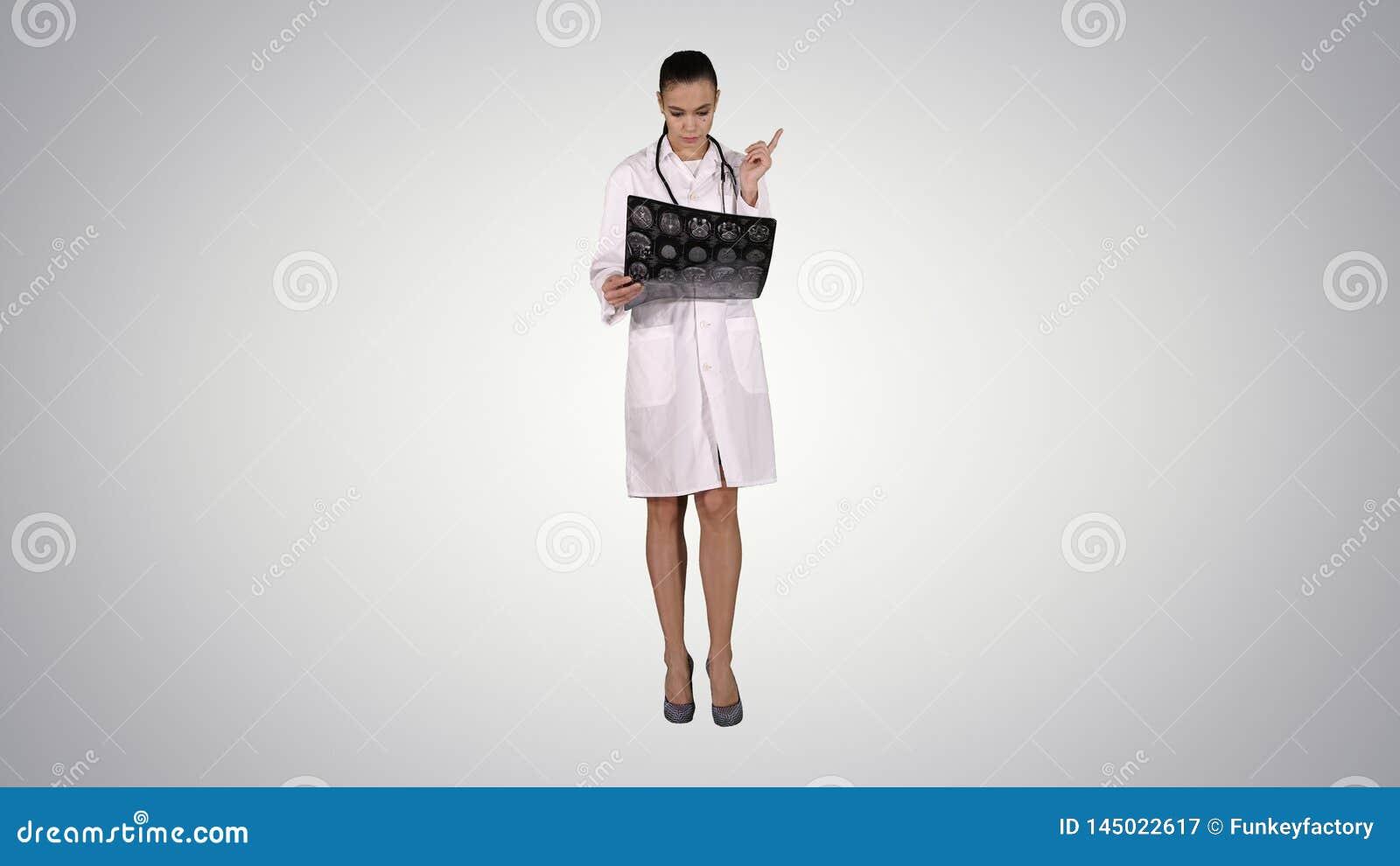 有白色labcoat的医生女性,看X-射线幅射线照相的图象,ct扫描,在梯度背景的mri