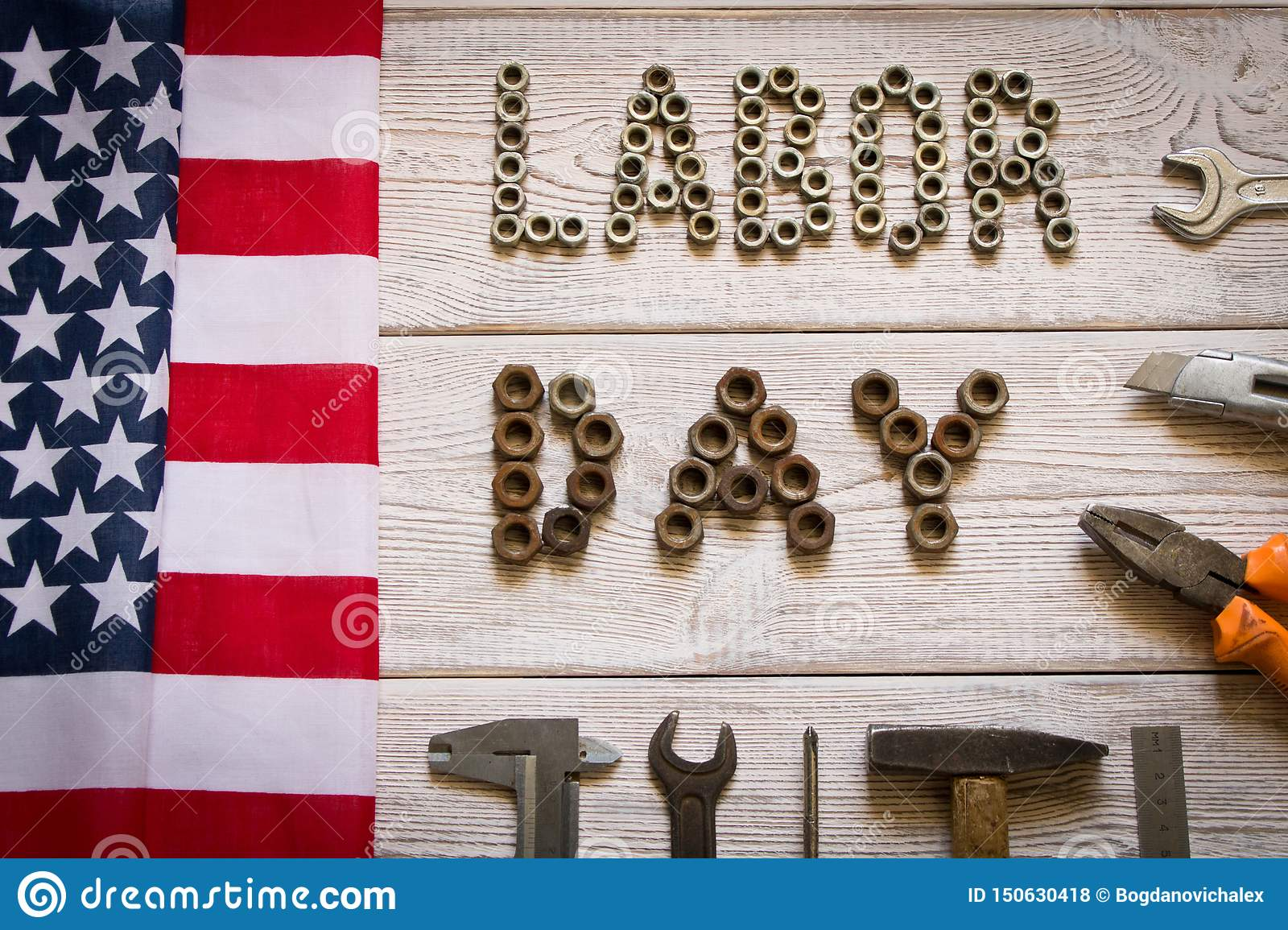 Labor day. American flag and Inscription labor day and various tools on a light wooden background