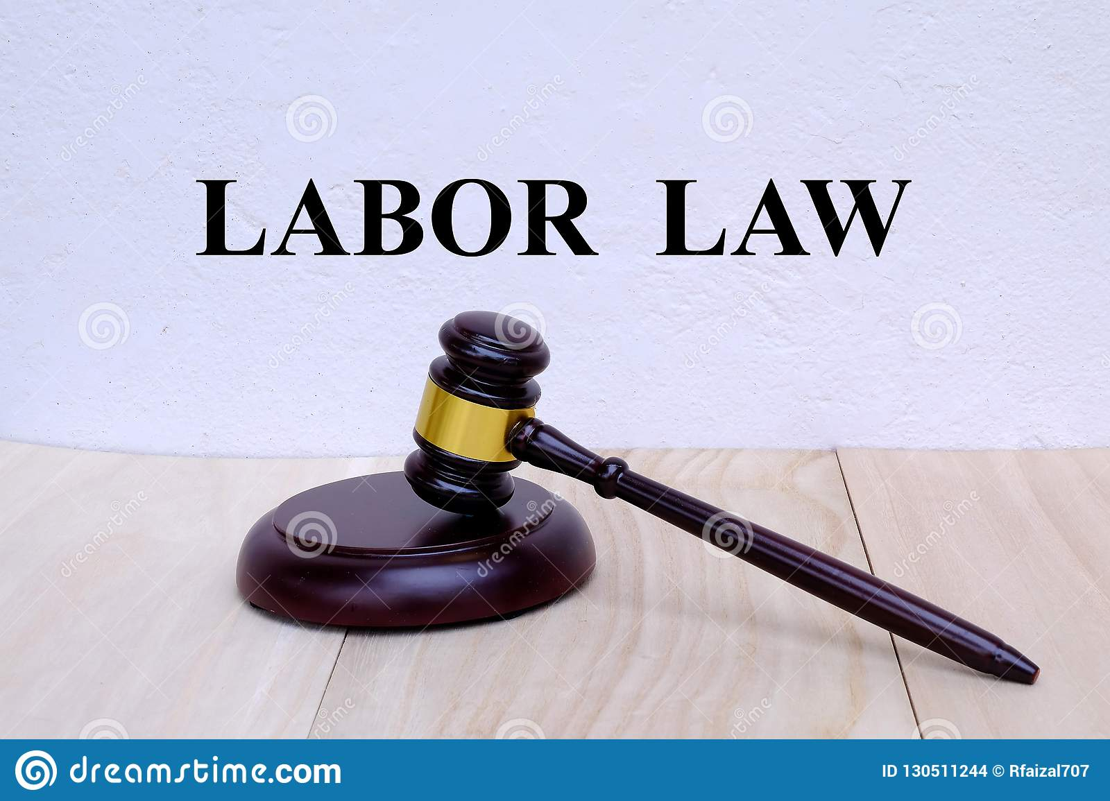 Labor Law written on the wall with gavel on wooden background. Law concept