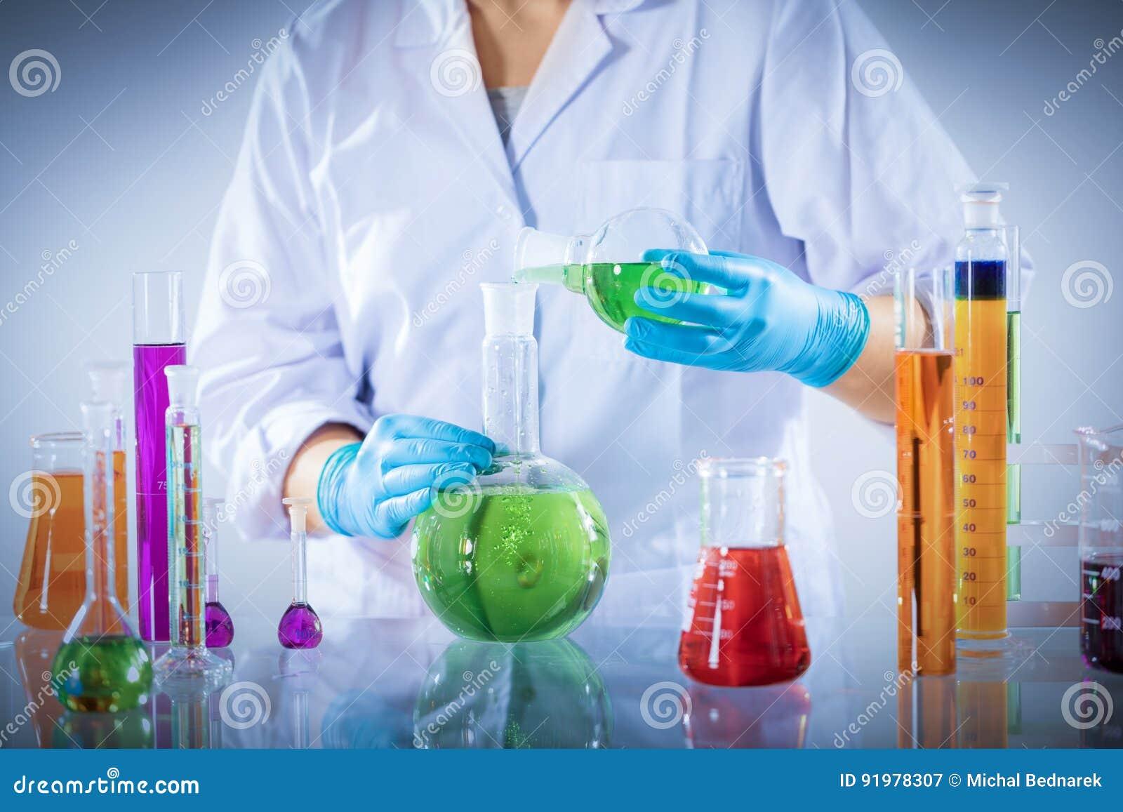 Laborancki pracownik miesza chemiczną ciekłą próbkę
