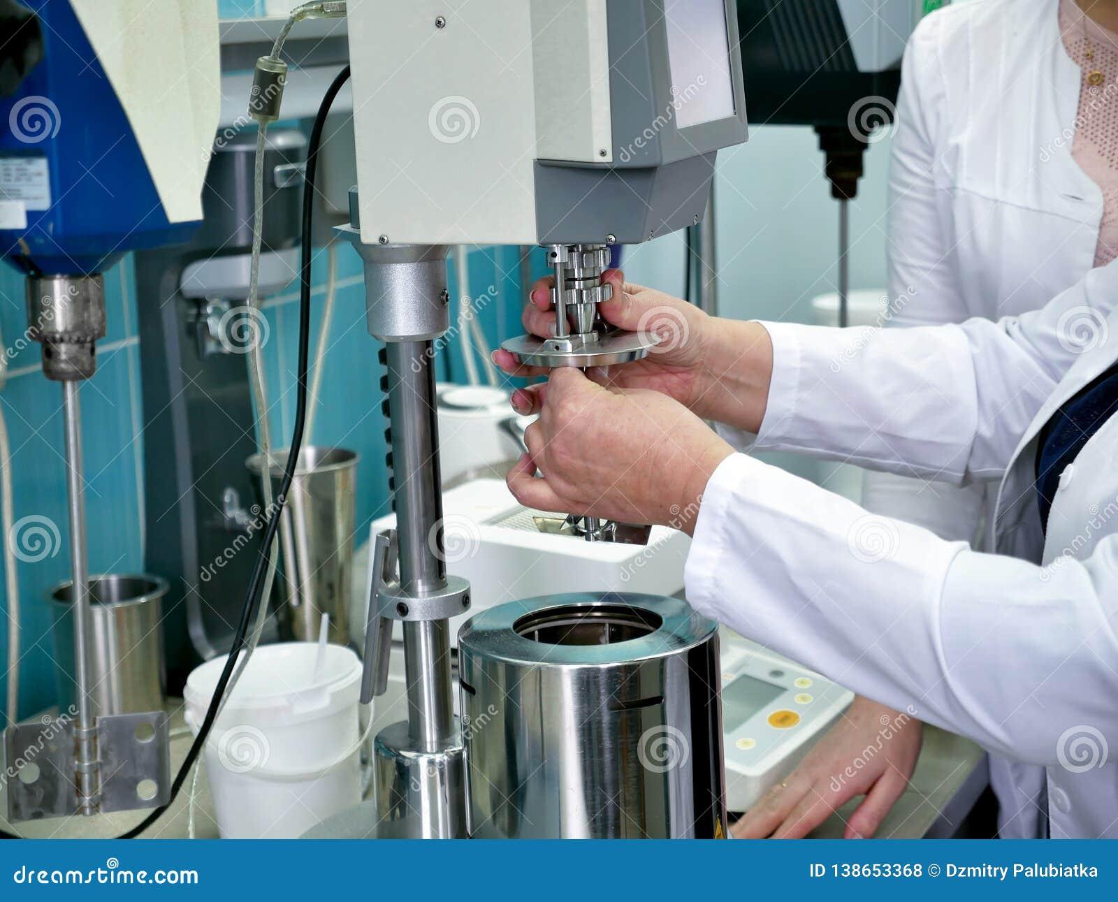Laboratorio su produzione chimica Laborandi ha messo l esperienza Le mani della persona che fa l esperimento