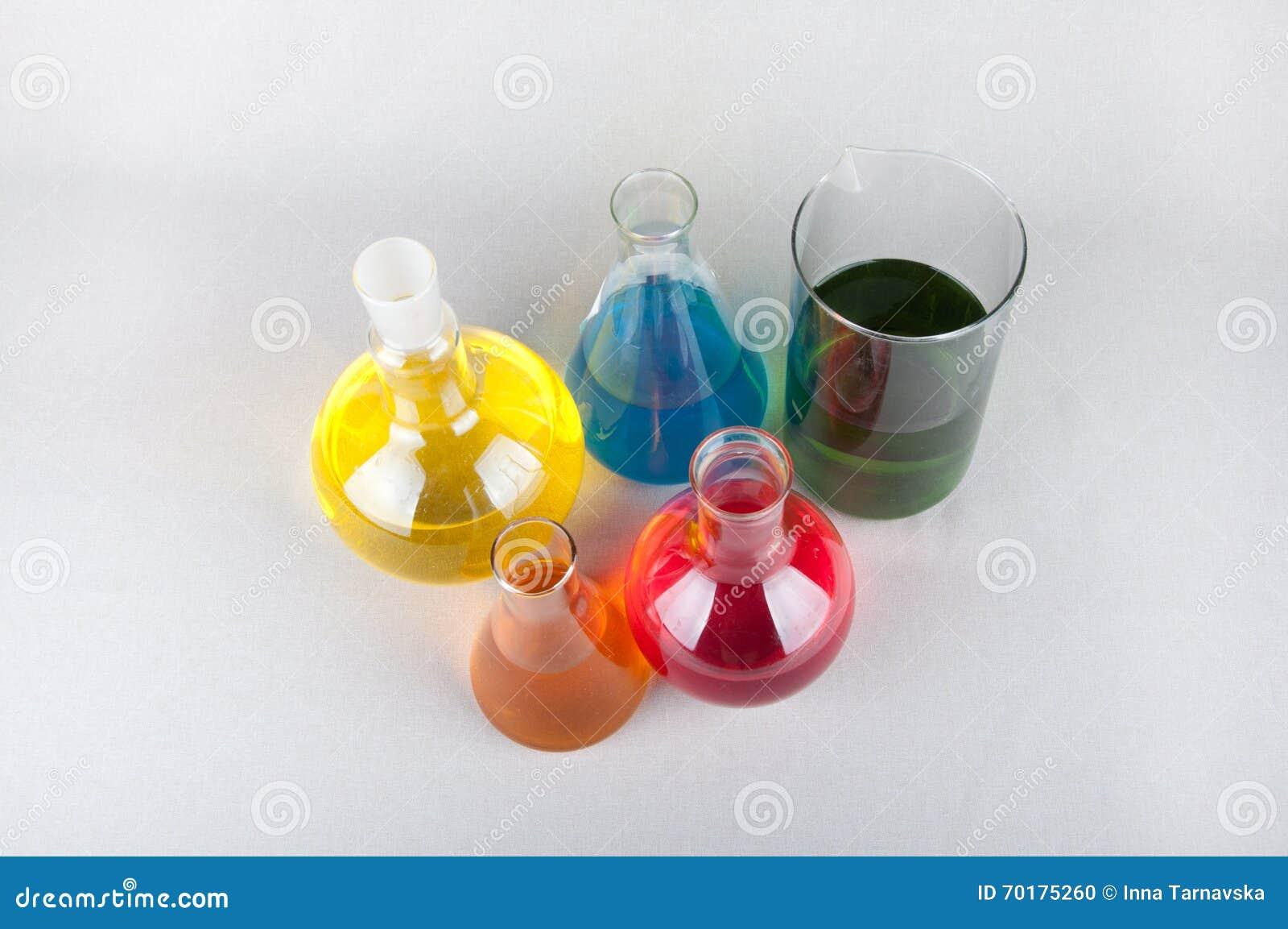 Laboratoriumflaskor med färgflytande på vit bakgrund