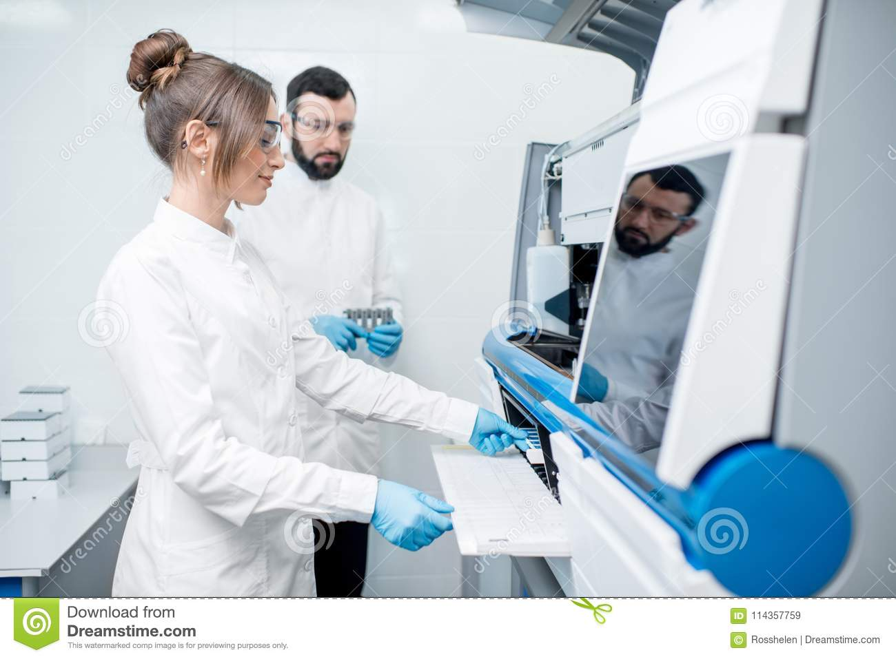 Laboratory assistants working with analizer