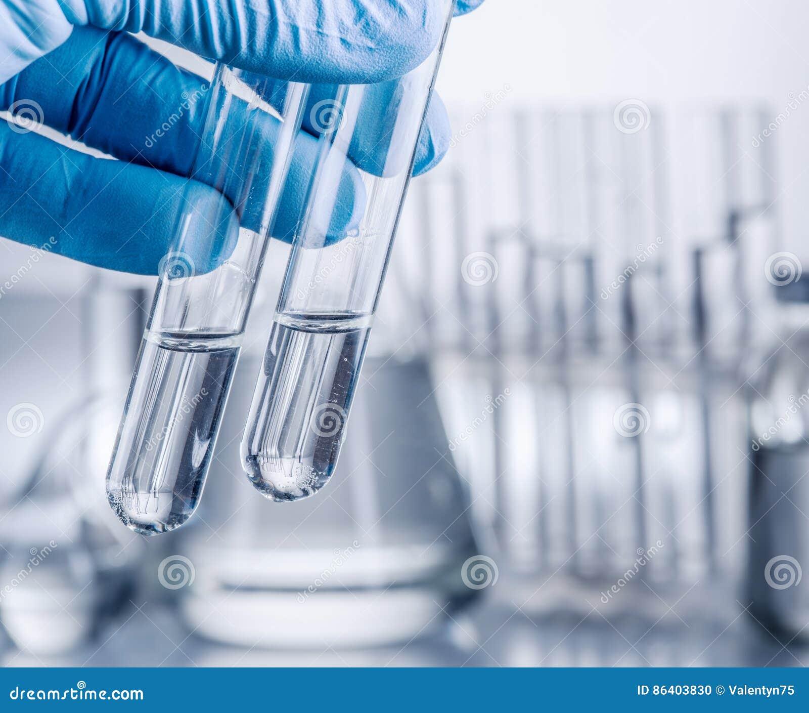 Laboratory beakers in analyst`s hand.