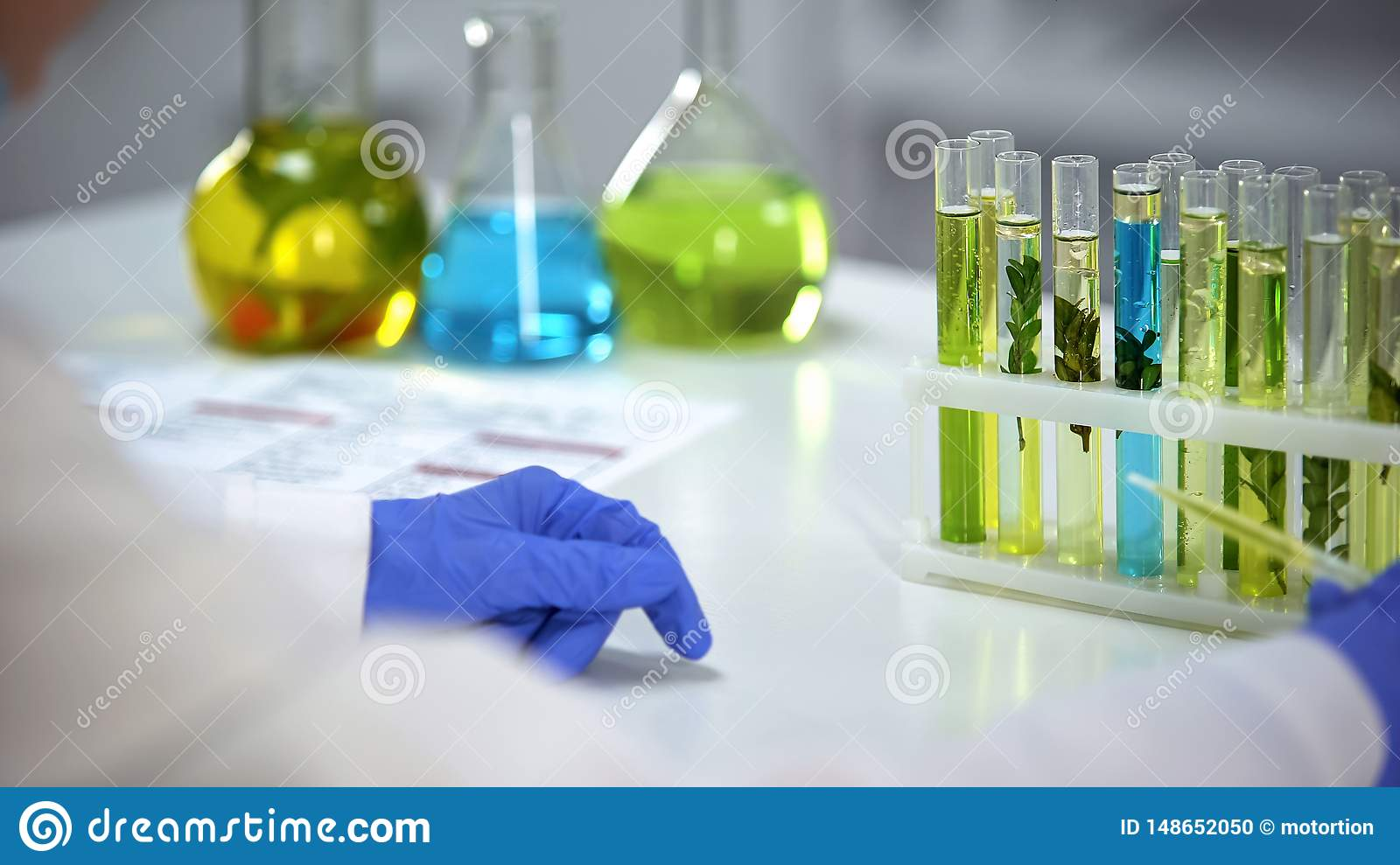 Laboratory worker holding dropper with oily yellow liquid, cosmetology extract