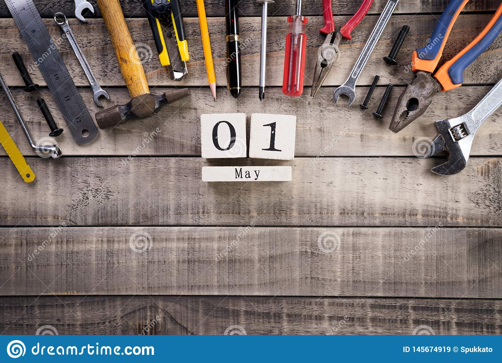 Labour Day, Wooden Block calendar with many handy tools on wooden background texture