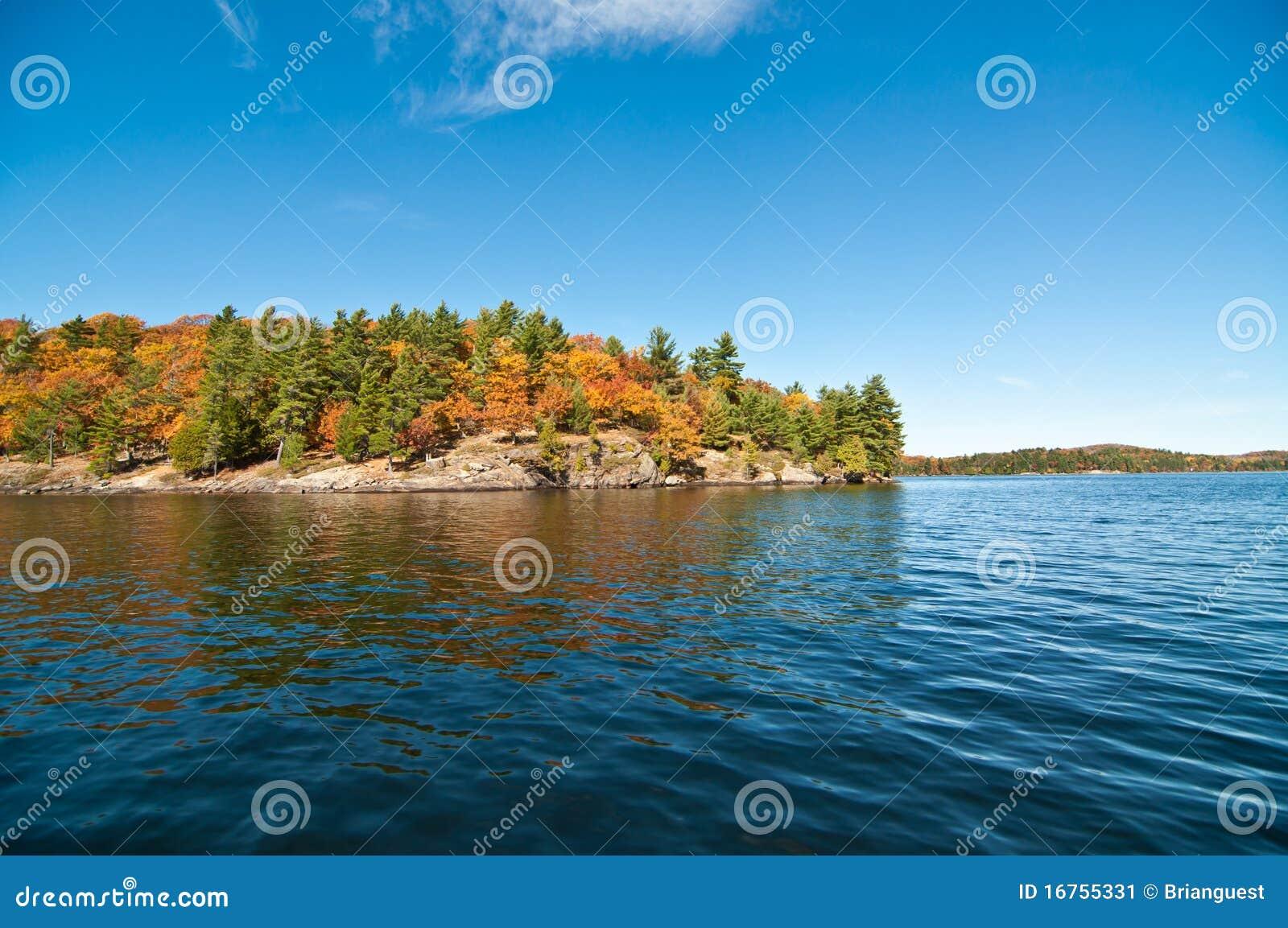 Lac canadien avec les couleurs d automne et le ciel bleu