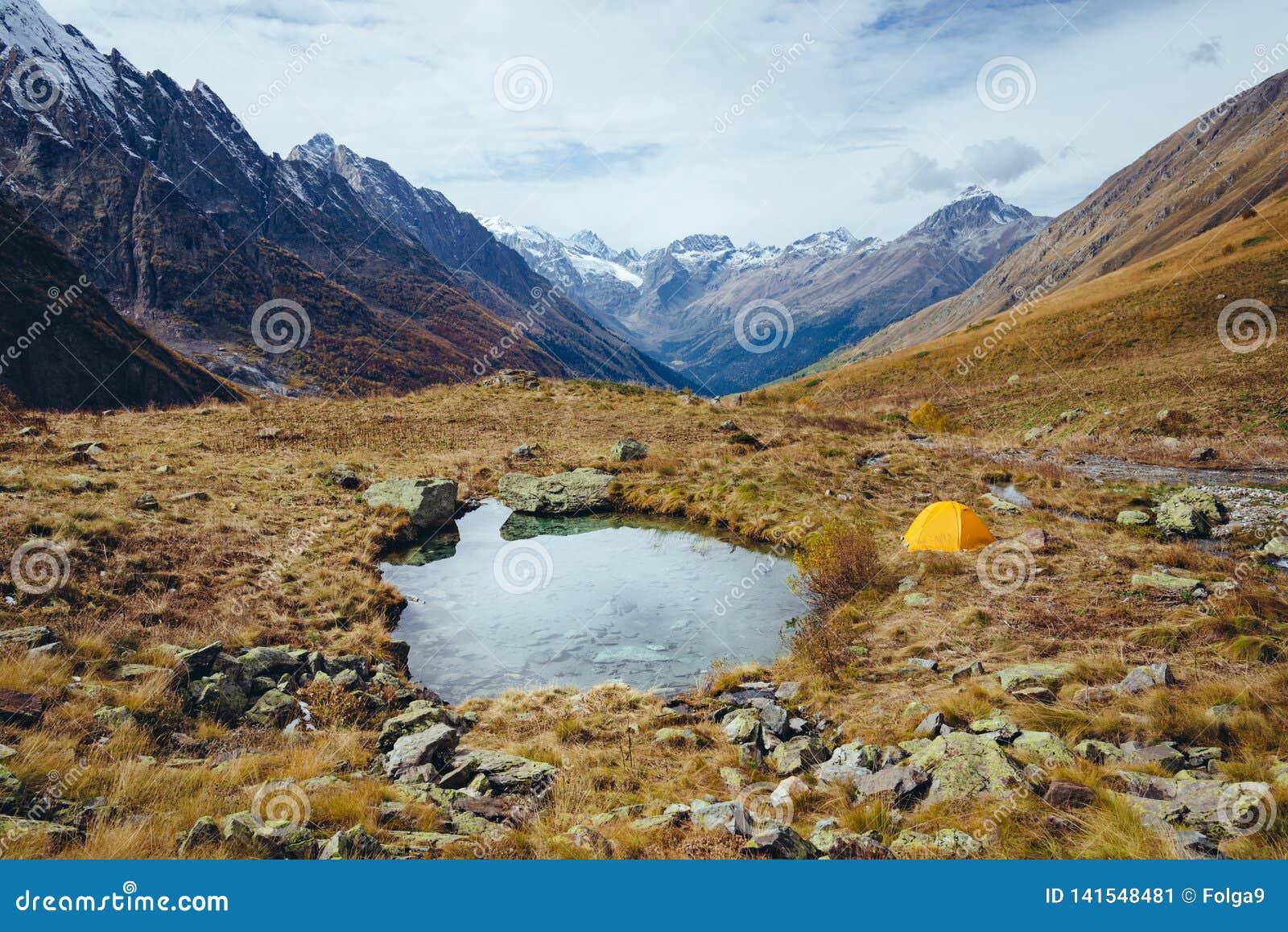 Lac dans les montagnes en automne et la tente jaune
