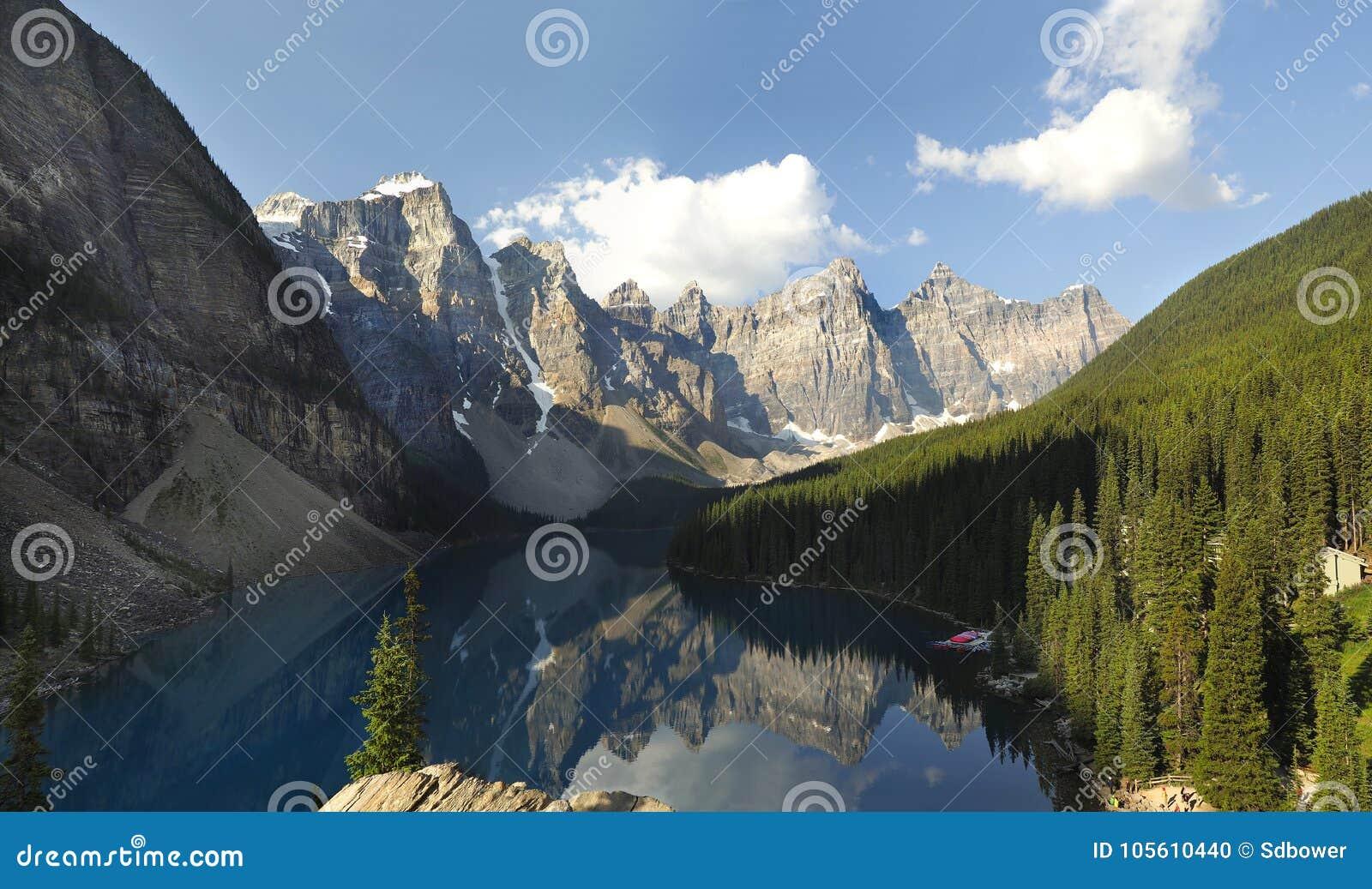 Lac moraine reflétant les montagnes environnantes