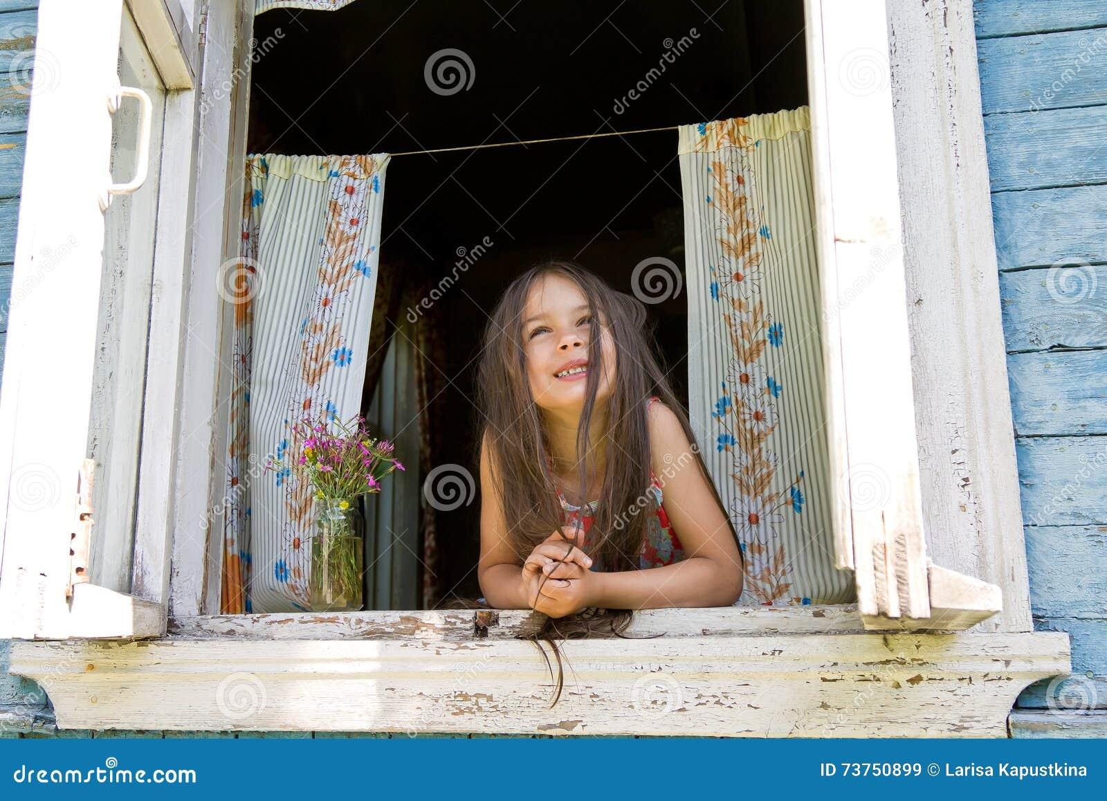 Lachend blij meisje die uit van het wijd open venster kijken