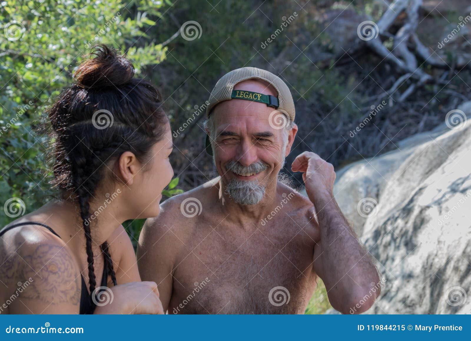 Lachend, glimlachend, hogere rijpe vader met Spaanse dochter buiten in aard die pret hebben samen
