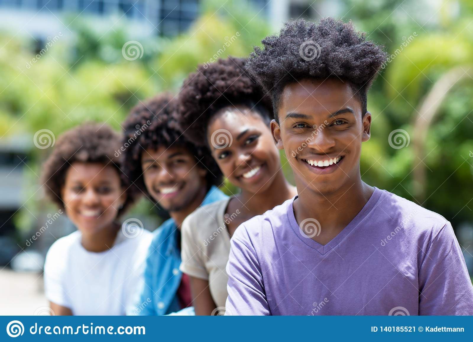 Lachende Afrikaanse Amerikaanse mens met groep jonge volwassenen in lijn