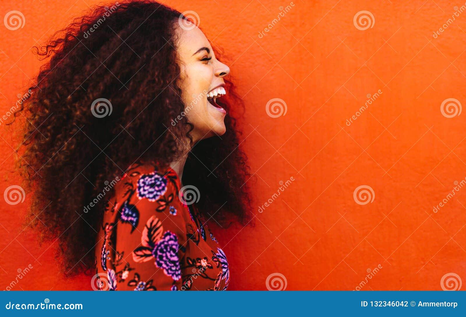 Lachende afrikanische junge Frau mit dem gelockten Haar