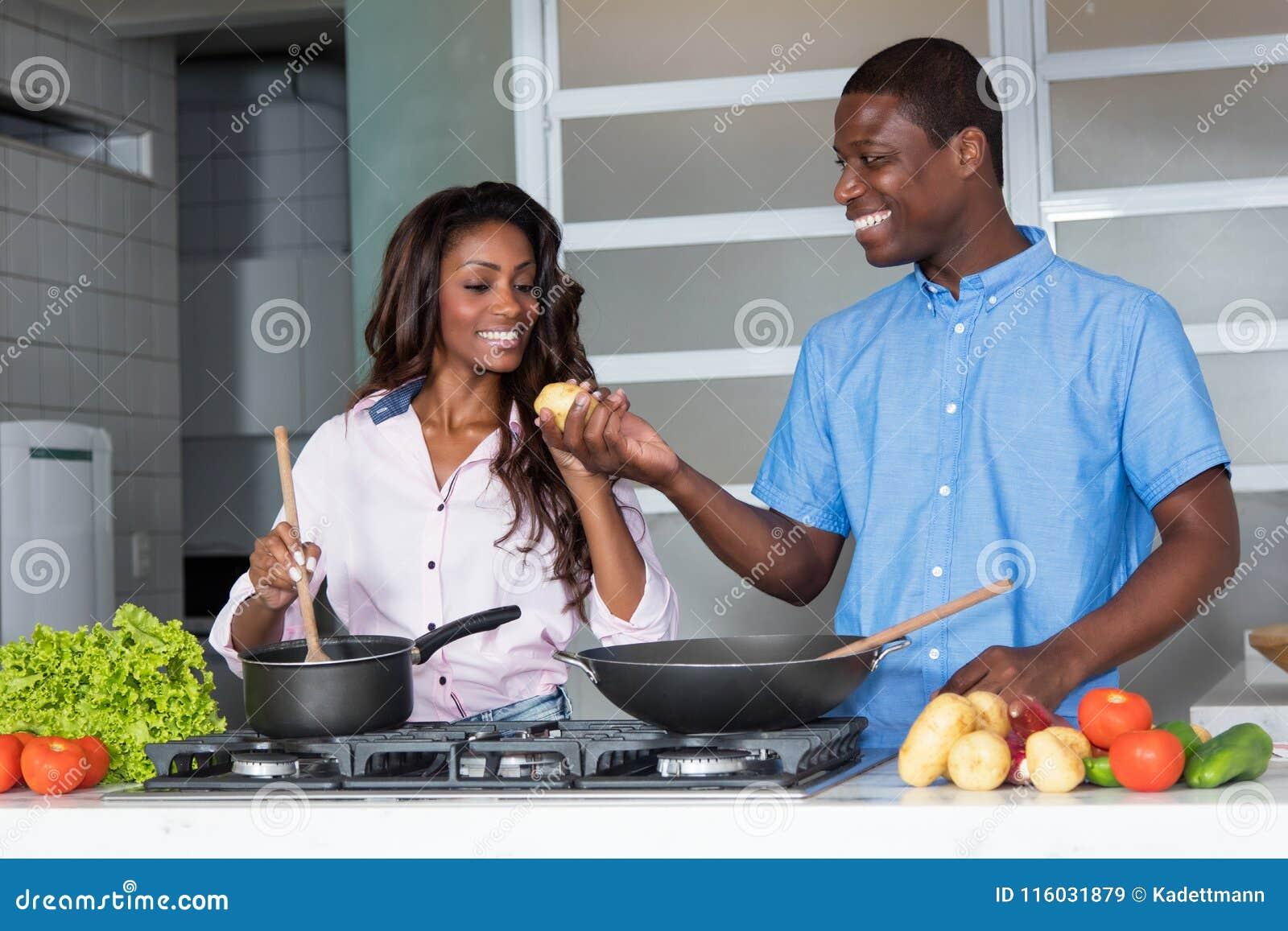 Lachende Afroamerikanerliebespaare, die an der Küche kochen