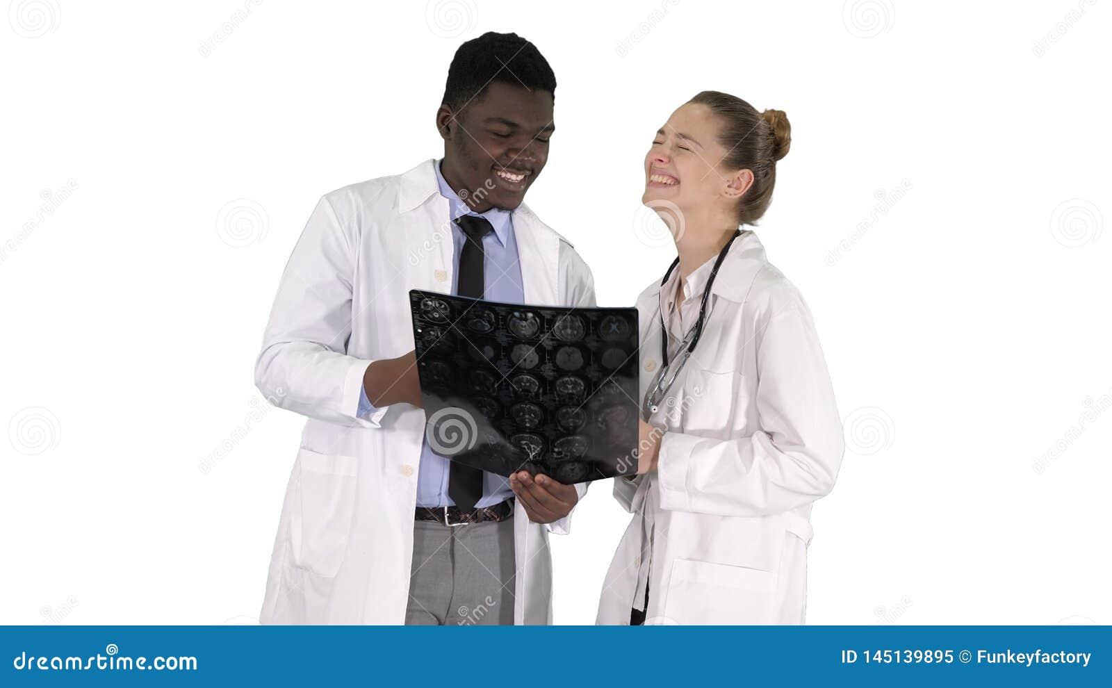 Lachende Doktoren, die R?ntgenstrahl auf wei?em Hintergrund studieren