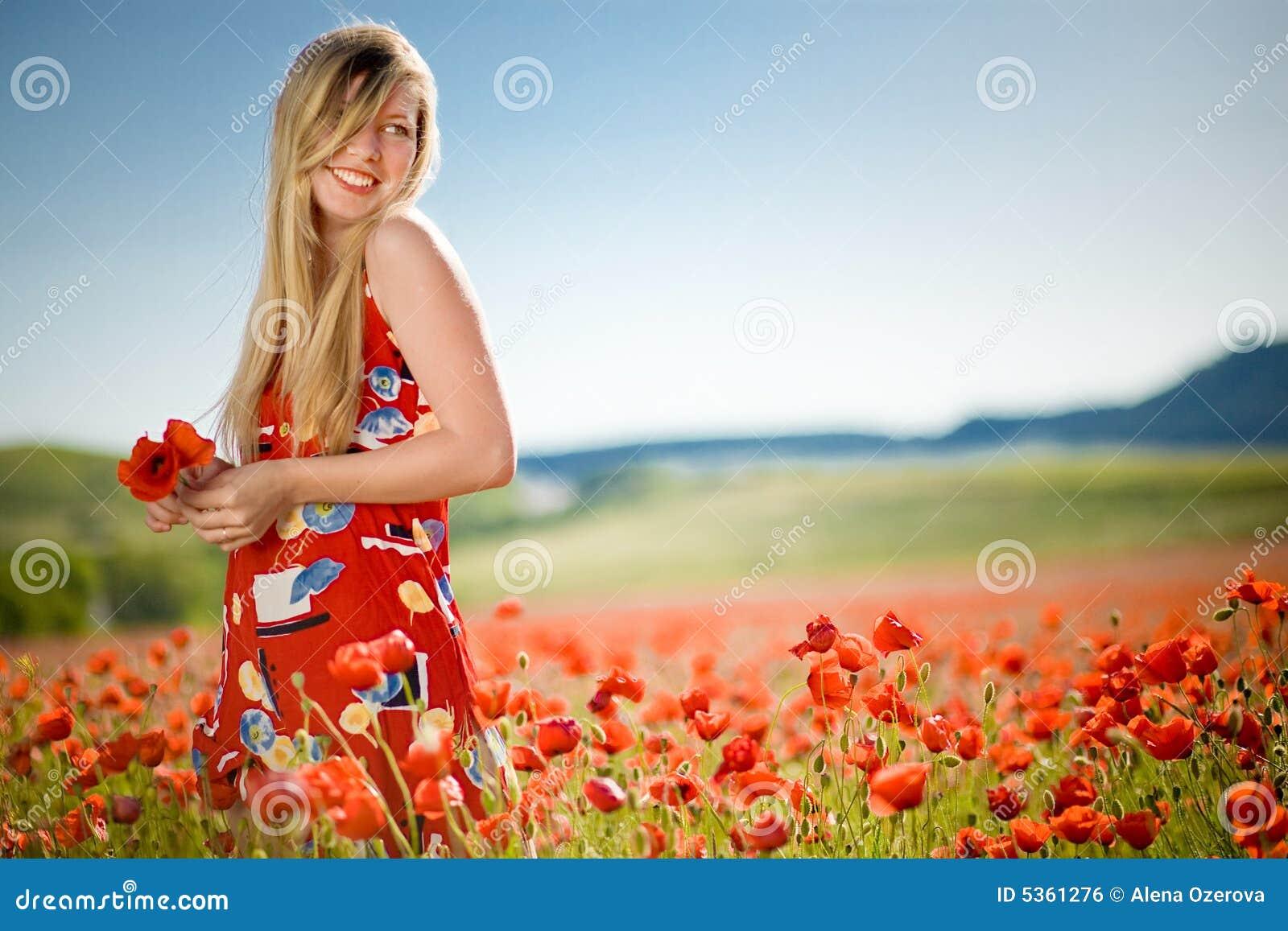 Lachende Frau auf dem Mohnblumegebiet
