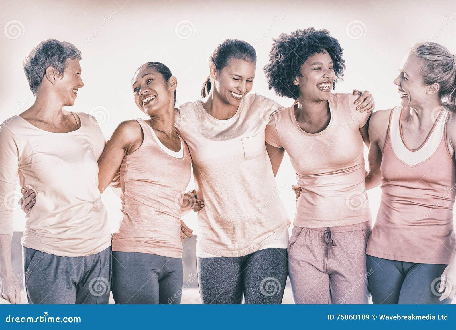 Lachende Frauen, die Rosa für Brustkrebs tragen