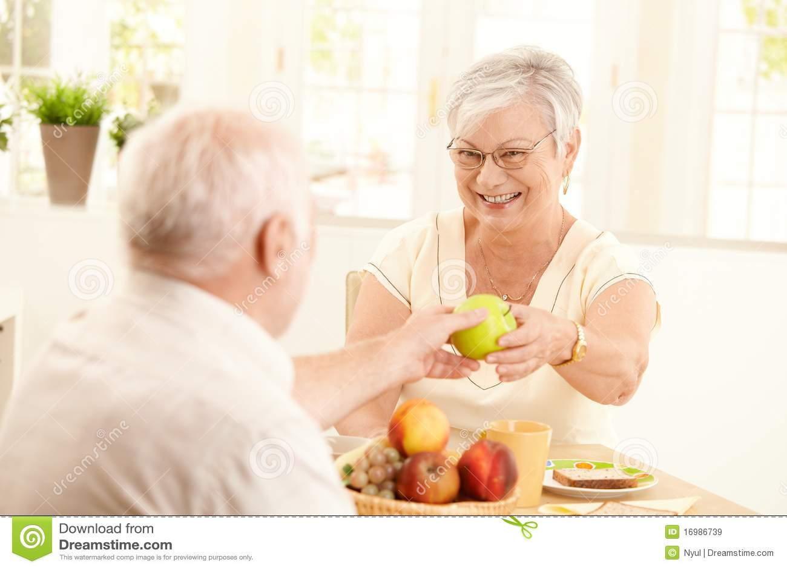 Lachende hogere vrouw die appel van echtgenoot krijgt