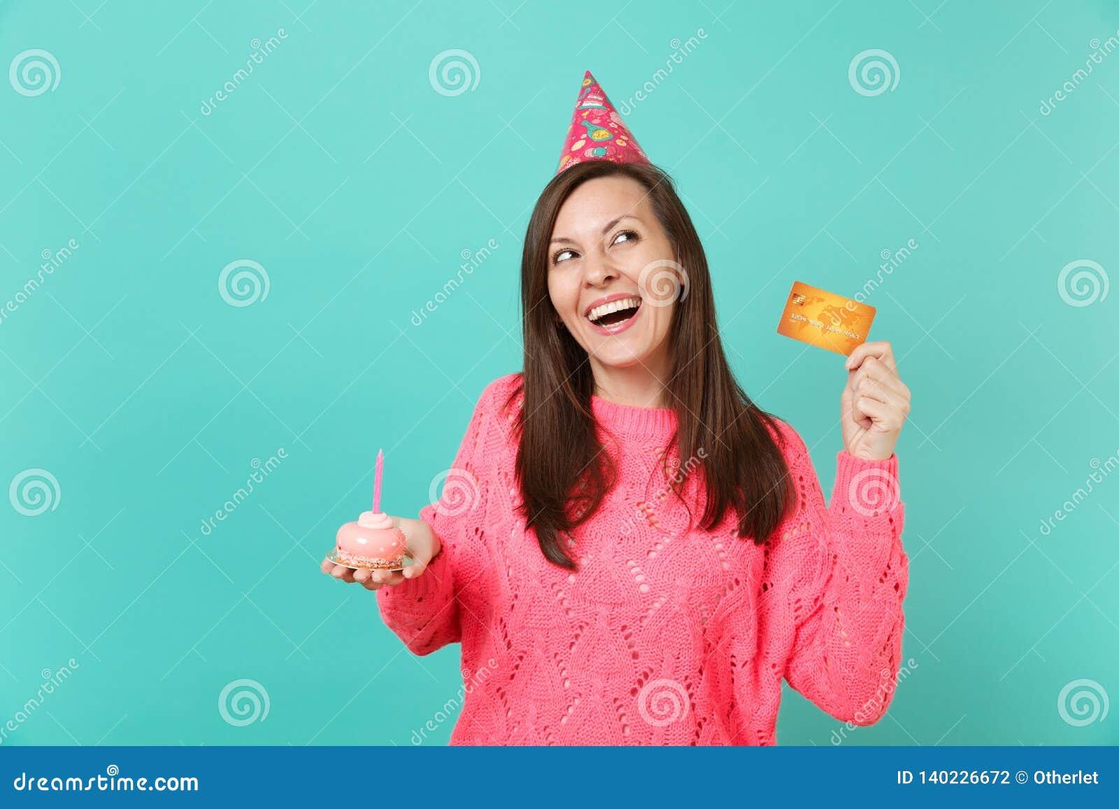 Lachende junge Frau im gestrickten rosa Strickjackengeburtstagshut, der oben in der Hand Kuchen des Griffs mit der Kerzenkreditka