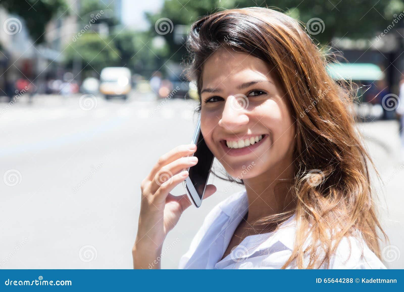 Lachende Kaukasische vrouw met mobiele telefoon in de stad
