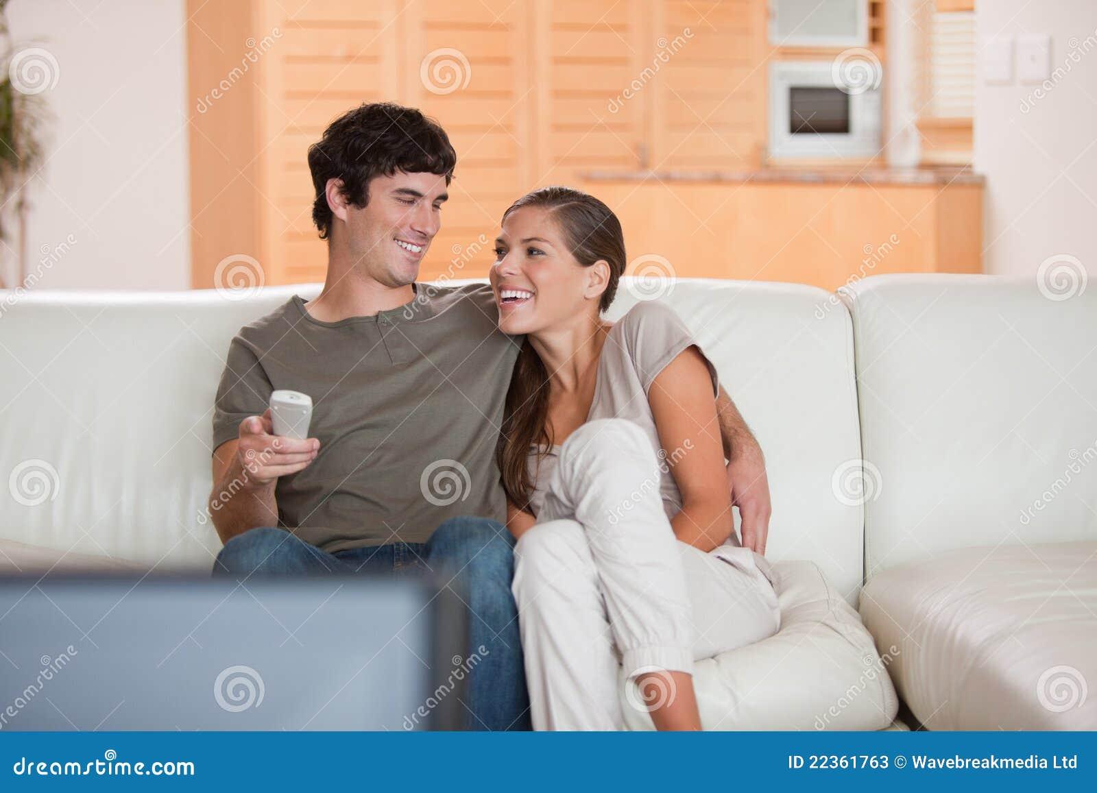 Lachende Paare, die zusammen lustigen Film überwachen