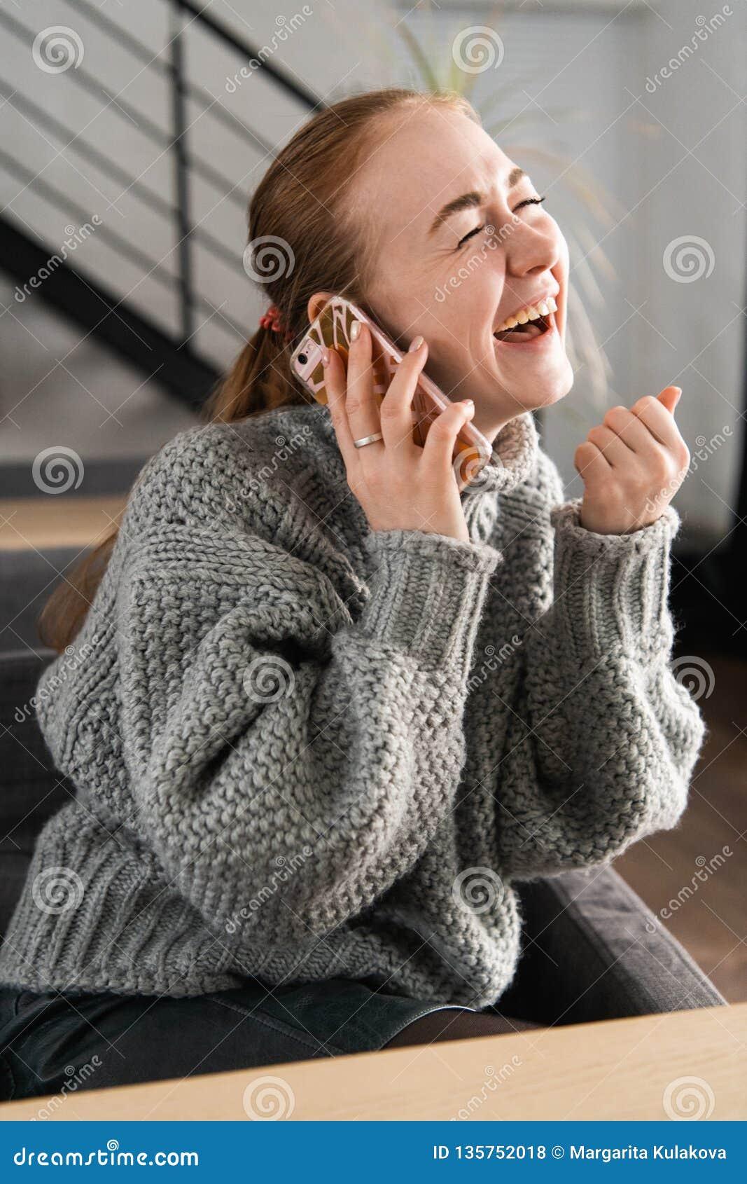 Lachende Rothaarige, die zu Hause auf der Couch hat ein Gespräch am Telefon sitzt