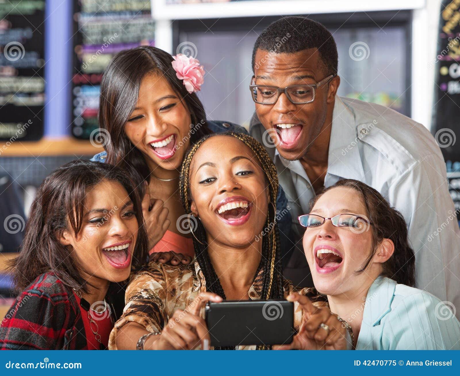 Lachende Studenten, die Smartphone halten