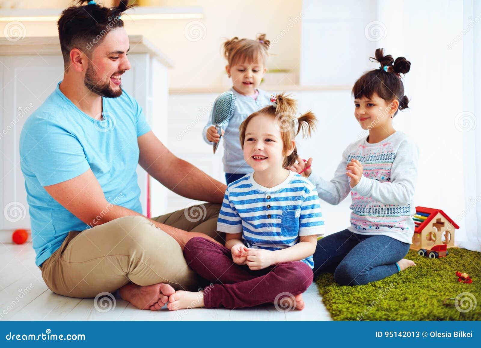 Lachende vader die met jonge geitjes gekke haarstijlen thuis maken