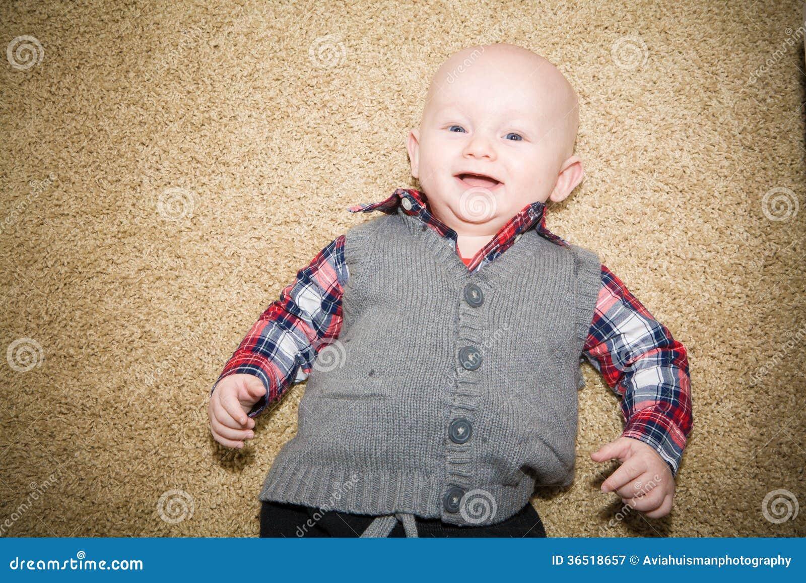 Lachendes Baby, das Gray Vest und kariertes Hemd trägt