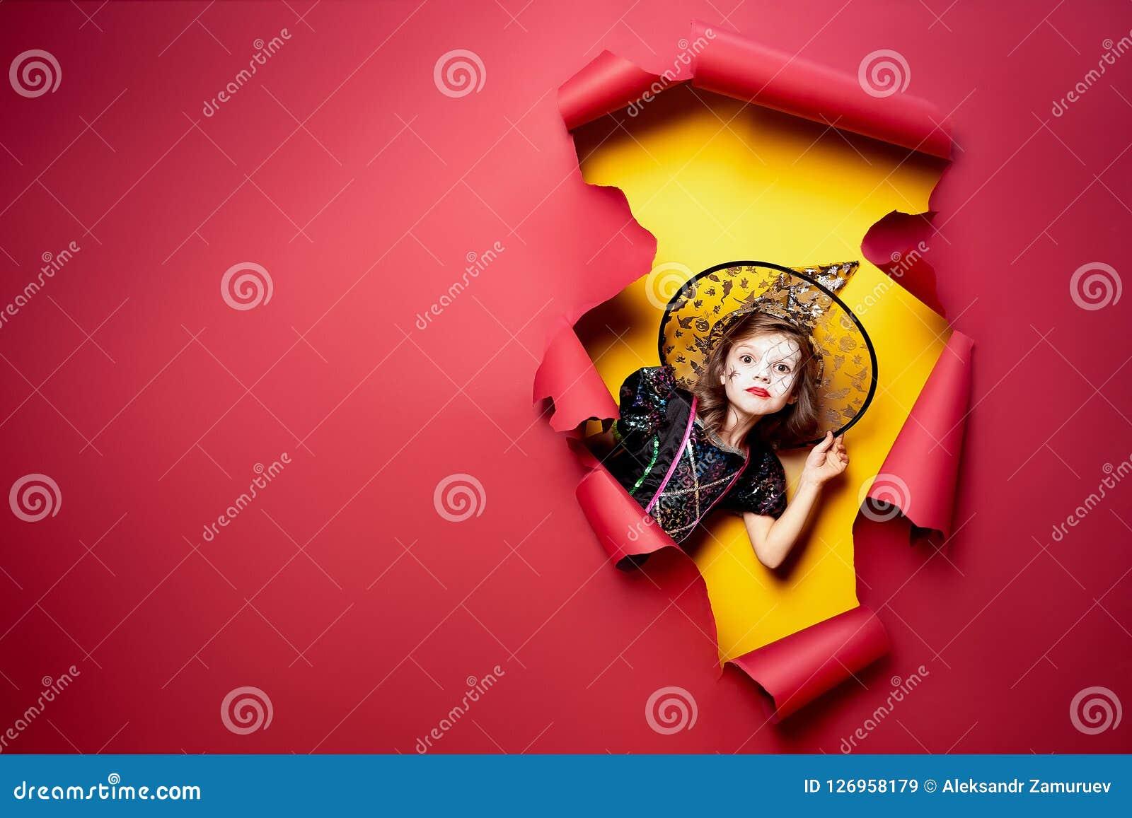 Lachendes lustiges Kindermädchen in einem Hexenkostüm in Halloween
