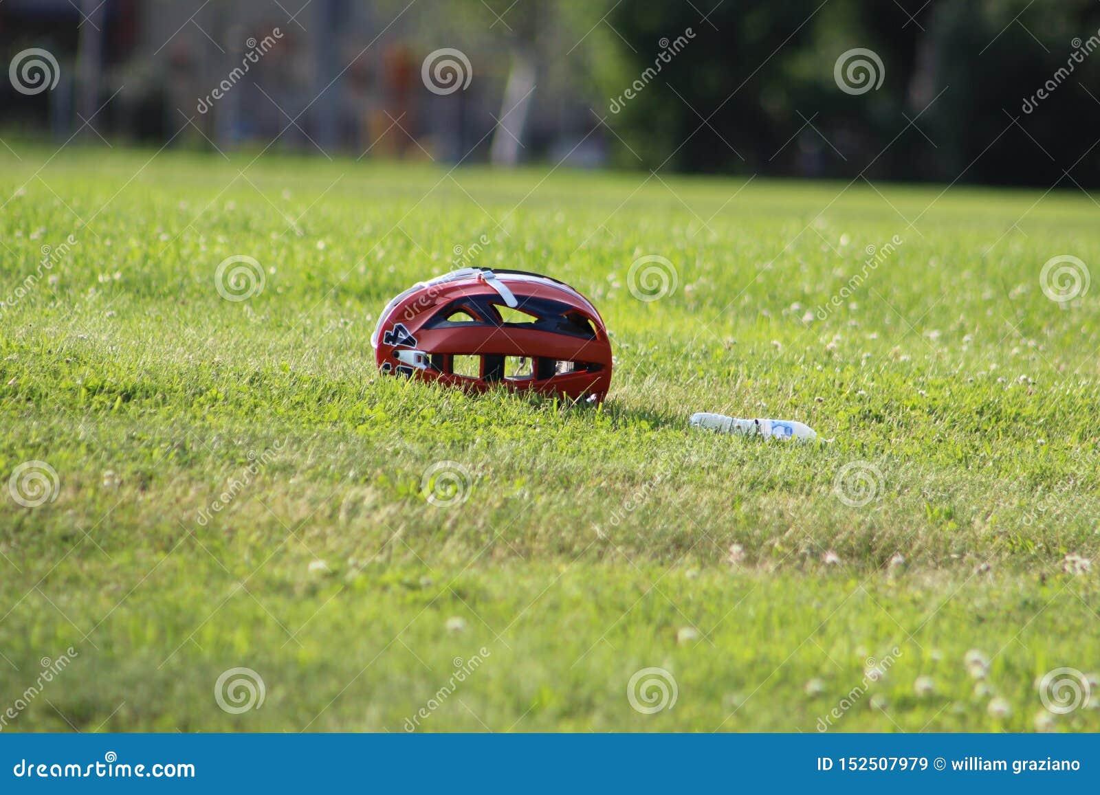 Lacrosse helmet on a grass field , with water bottle.