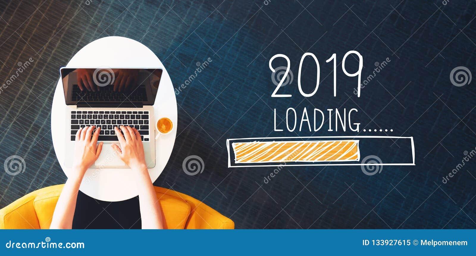 Ladda det nya året 2019 med personen som använder en bärbar dator
