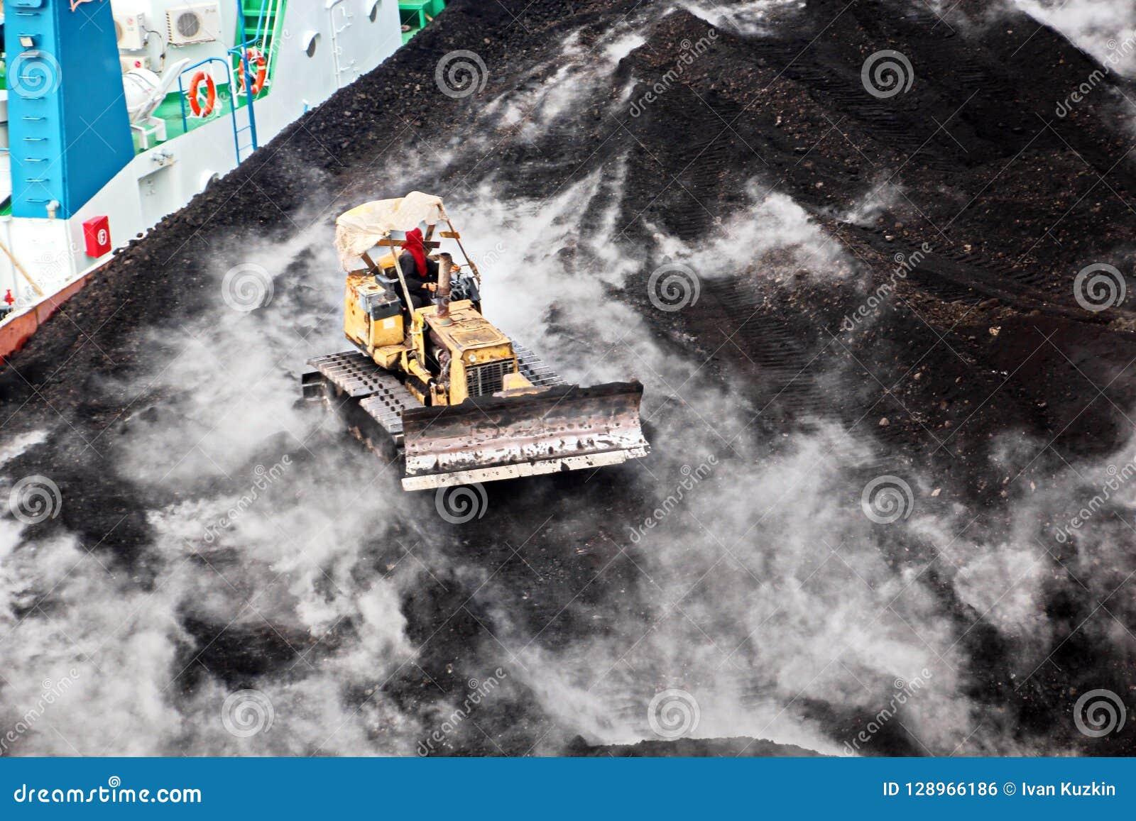Ladda kol från lastpråm på en bärare som i stora partier använder skeppkranar och hastiga grepp på porten av Samarinda, Indonesie