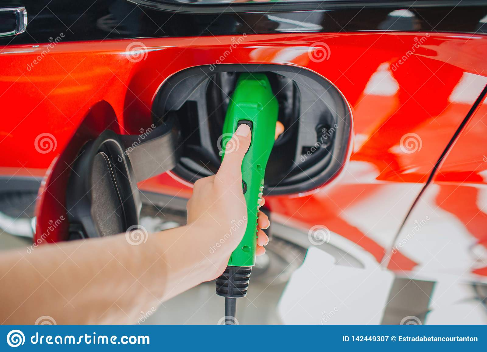 Laddande elektriskt stationsmedel Närbilden av kvinnahanden som laddar en elbil med tillförselen för maktkabel, pluggade
