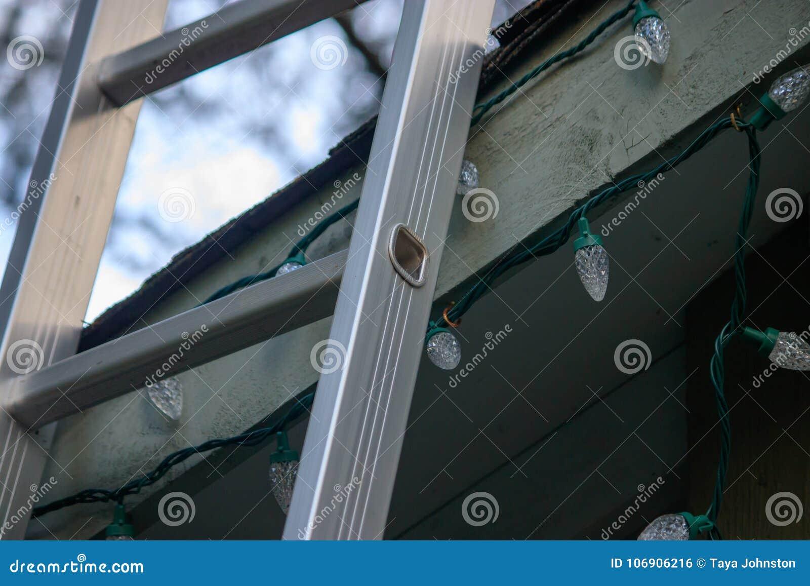 Ladder die omhoog op dak voor Kerstmis leunen te verfraaien