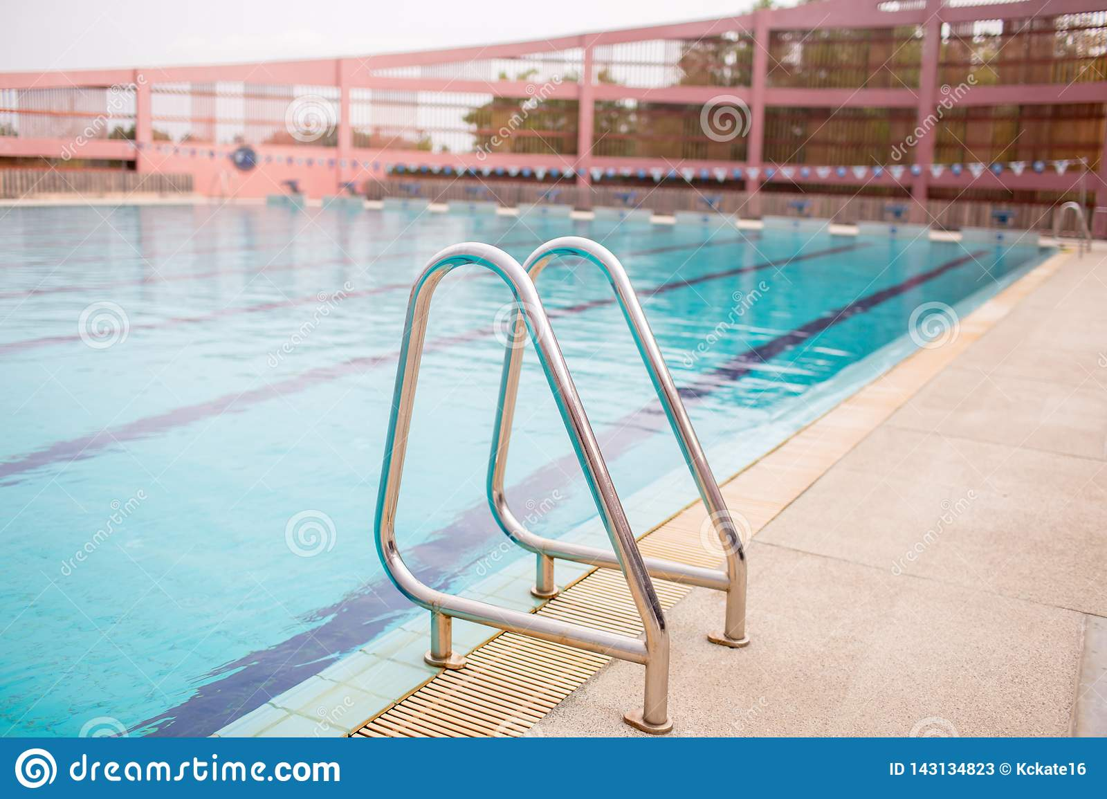 Ladder stainless handrails for descent into swimming pool. Swimming pool with handrail.