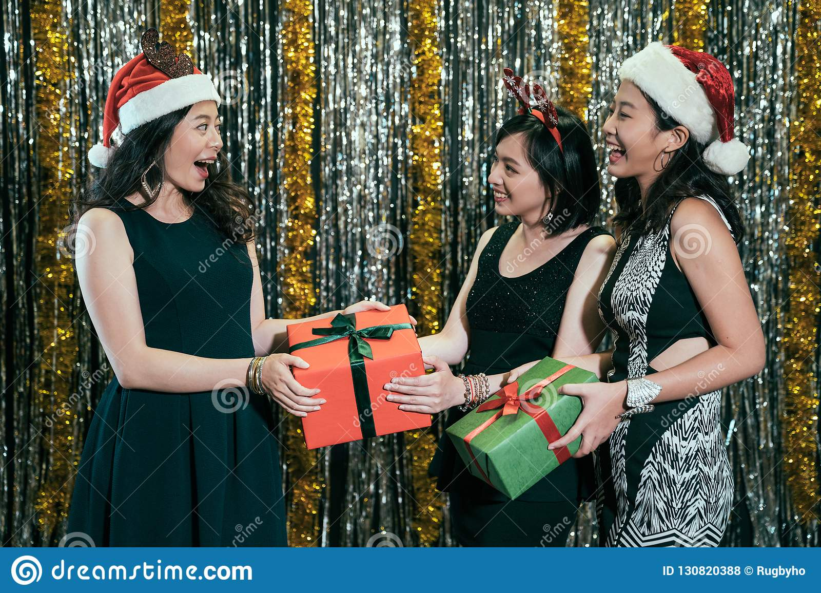 Ladies Christmas Gifts.Ladies With Santa Hats Exchange Christmas Gifts Stock Photo